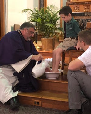 """Just as Jesus did with his disciples, Father Larry McBride washes the feet of student Eastin Fulkerson as Holy Name School Principal Scottie Koonce looks on. """"This reminds us of our calling to be a servant and friend to those around us,"""" wrote Holy Name School's Emma Bridges in an email to The Gleaner. The same was done with a teacher from the school. This ceremony was part of Wednesday's Holy Week Mass for students and faculty at Holy Name Catholic School."""