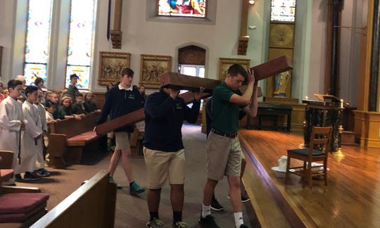 Eighth-grade boys from Holy Name School carry a cross into the sanctuary at Holy Name of Jesus Catholic Church during a special Holy Week Mass for students and faculty on Wednesday. Carrying the cross is meant to be a tangible reminder to the students of Jesus' crucifixion.