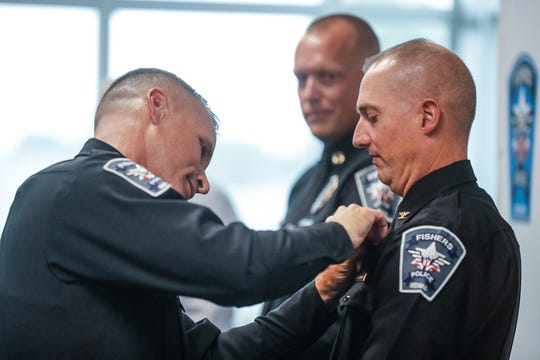 New Fishers Police chief, Ed Gebhart, left, pins badges on newly promoted Fishers Assistant Police Chief, Luke Gannon, right, and new Fishers Police Captain, Mike Pedersen, center, during a promotion ceremony at the new Fishers Police Station, 1 Municipal Drive, Fishers, Ind., on Friday, Sept. 7, 2018.