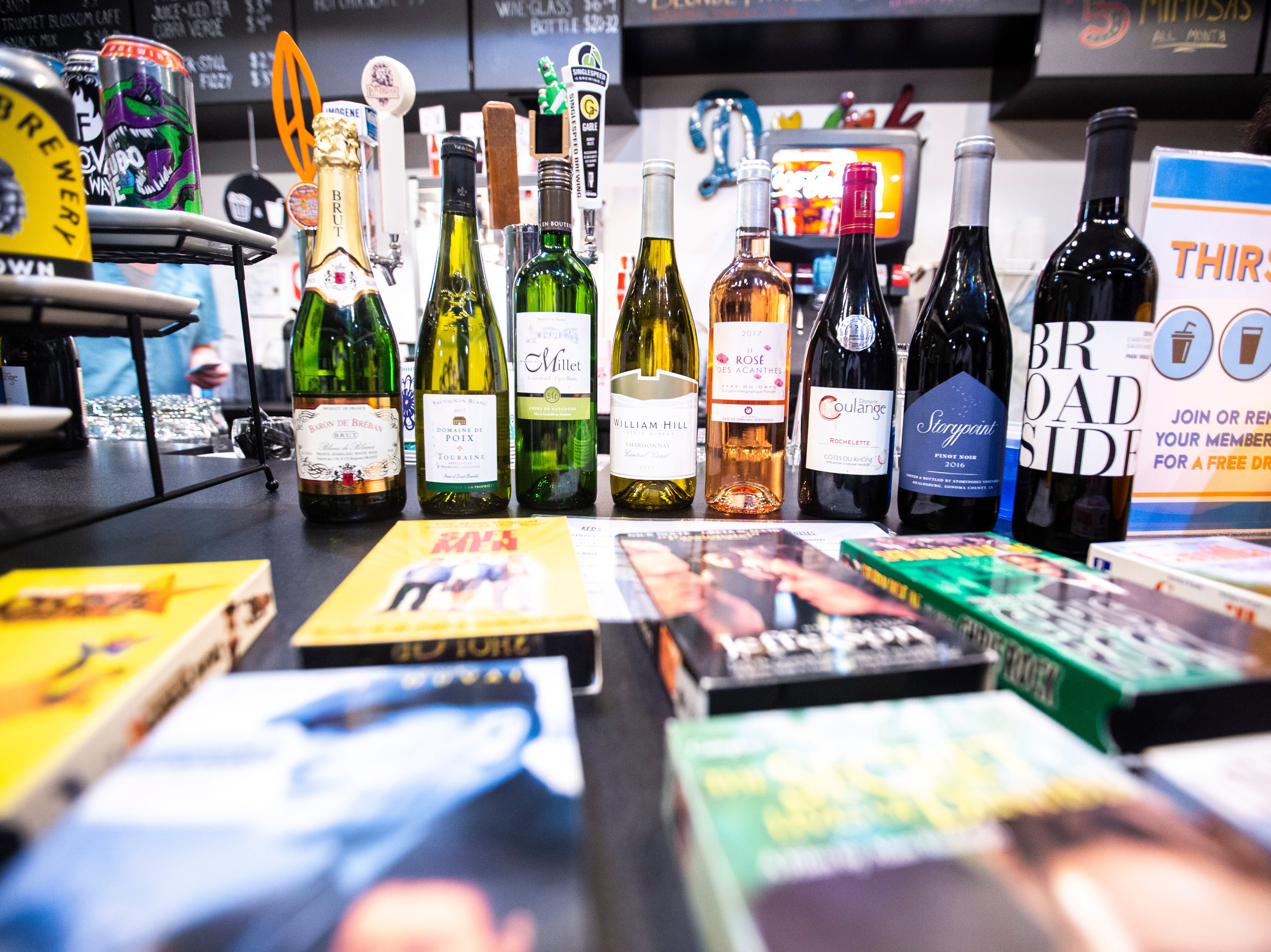 """Bottles of wine sit on a counter behind a variety of VHS tapes during a """"Late Shift at the Grindhouse"""" movie screening, Wednesday, April 17, 2019, at FilmScene in Iowa City, Iowa."""