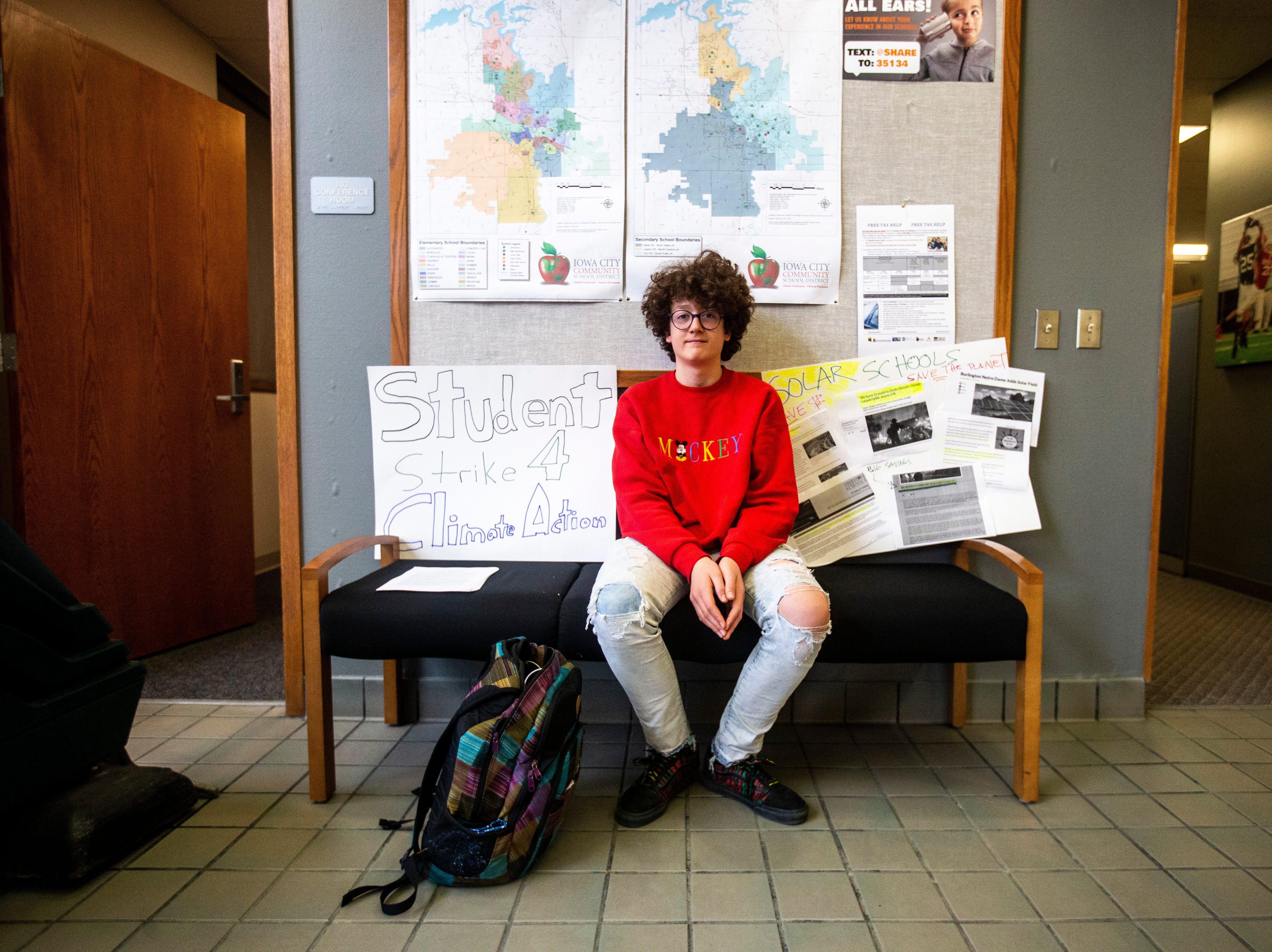 Massimo Paciotto-Biggers, 13, sits for a photo during a weekly walkout demanding solar panels on school buildings, Friday, April 5, 2019, outside the Iowa City Community School District offices along North Dodge Street in Iowa City, Iowa. Paciotto-Biggers sat by himself that afternoon.