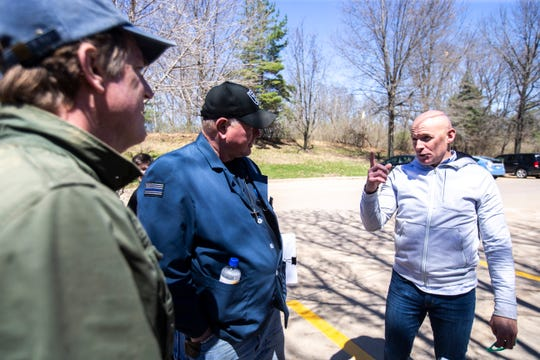 Former Hawkeye, NFL and City High star Tim Dwight, far right, speaks to school board member Phil Hemingway, and Jeff Biggers during a weekly walkout demanding solar panels on school buildings, Friday, April 19, 2019, outside the Iowa City Community School District offices along North Dodge Street in Iowa City, Iowa.