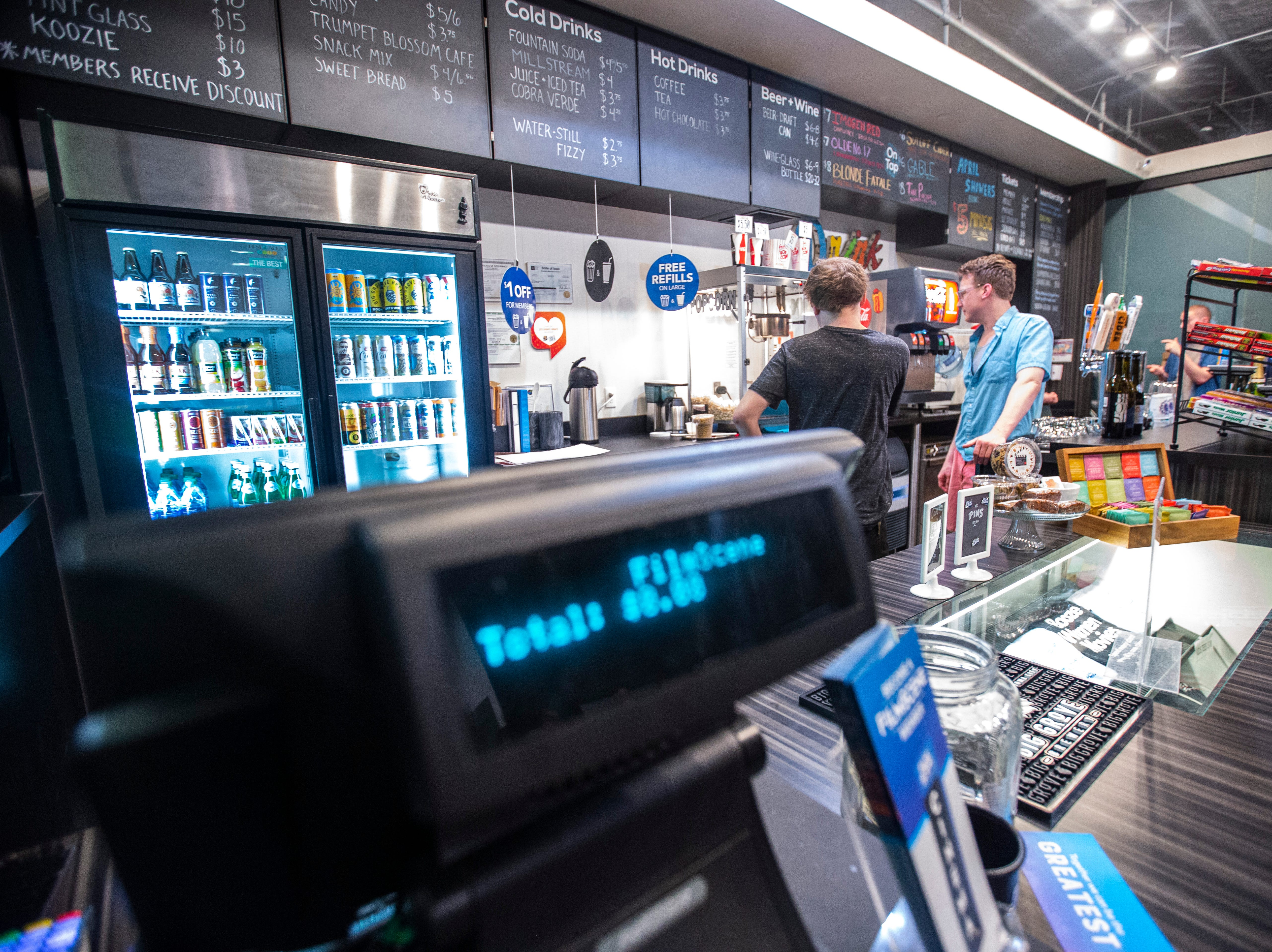 """""""FilmScene"""" scrolls across point of sale display while Aaron Holmgren, assistant operations manager, and Max Johnson, right, work during a """"Late Shift at the Grindhouse"""" movie screening, Wednesday, April 17, 2019, at FilmScene in Iowa City, Iowa."""