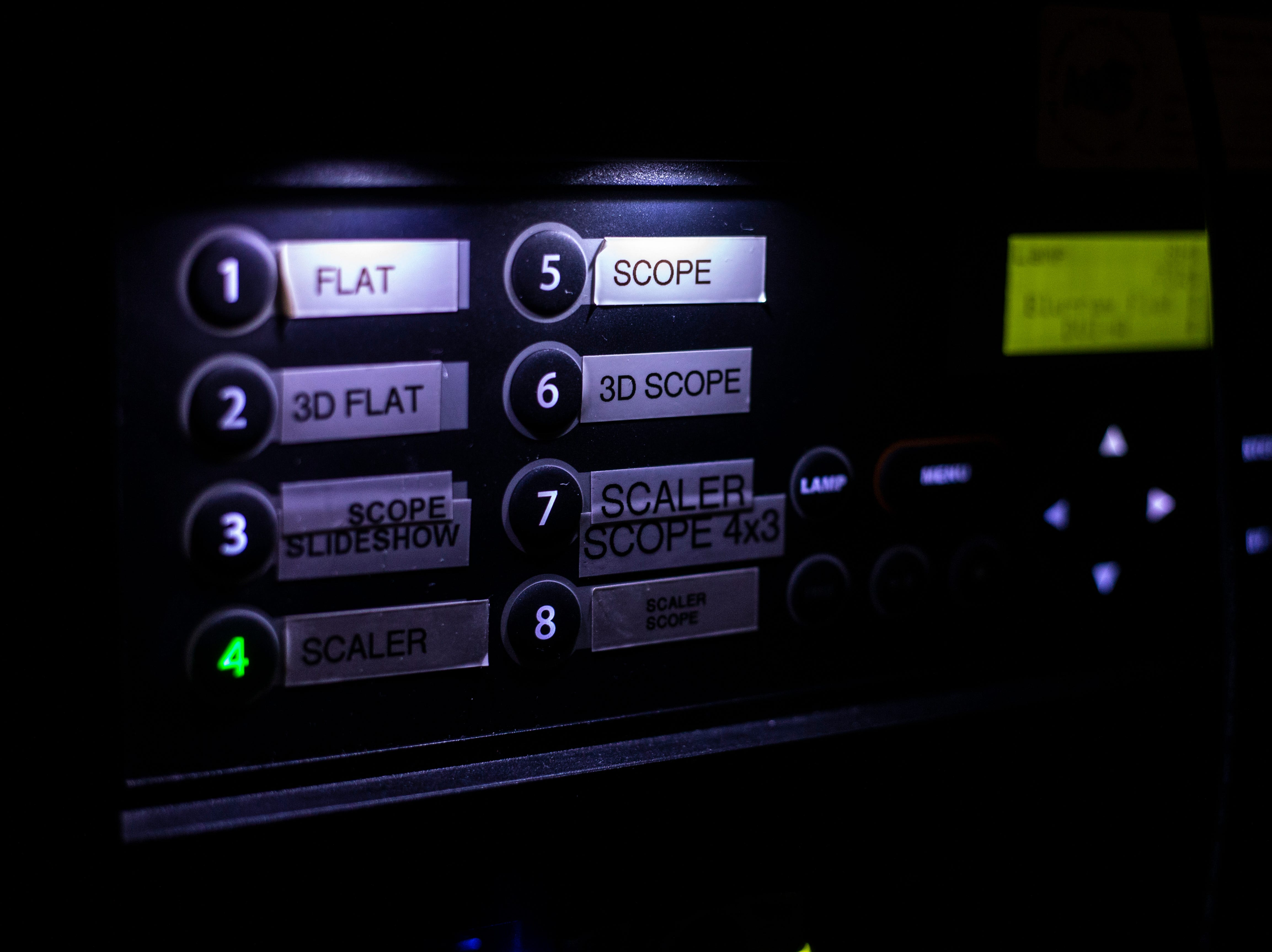 """Buttons are illuminated in the projection room during a """"Late Shift at the Grindhouse"""" movie screening, Wednesday, April 17, 2019, at FilmScene in Iowa City, Iowa."""
