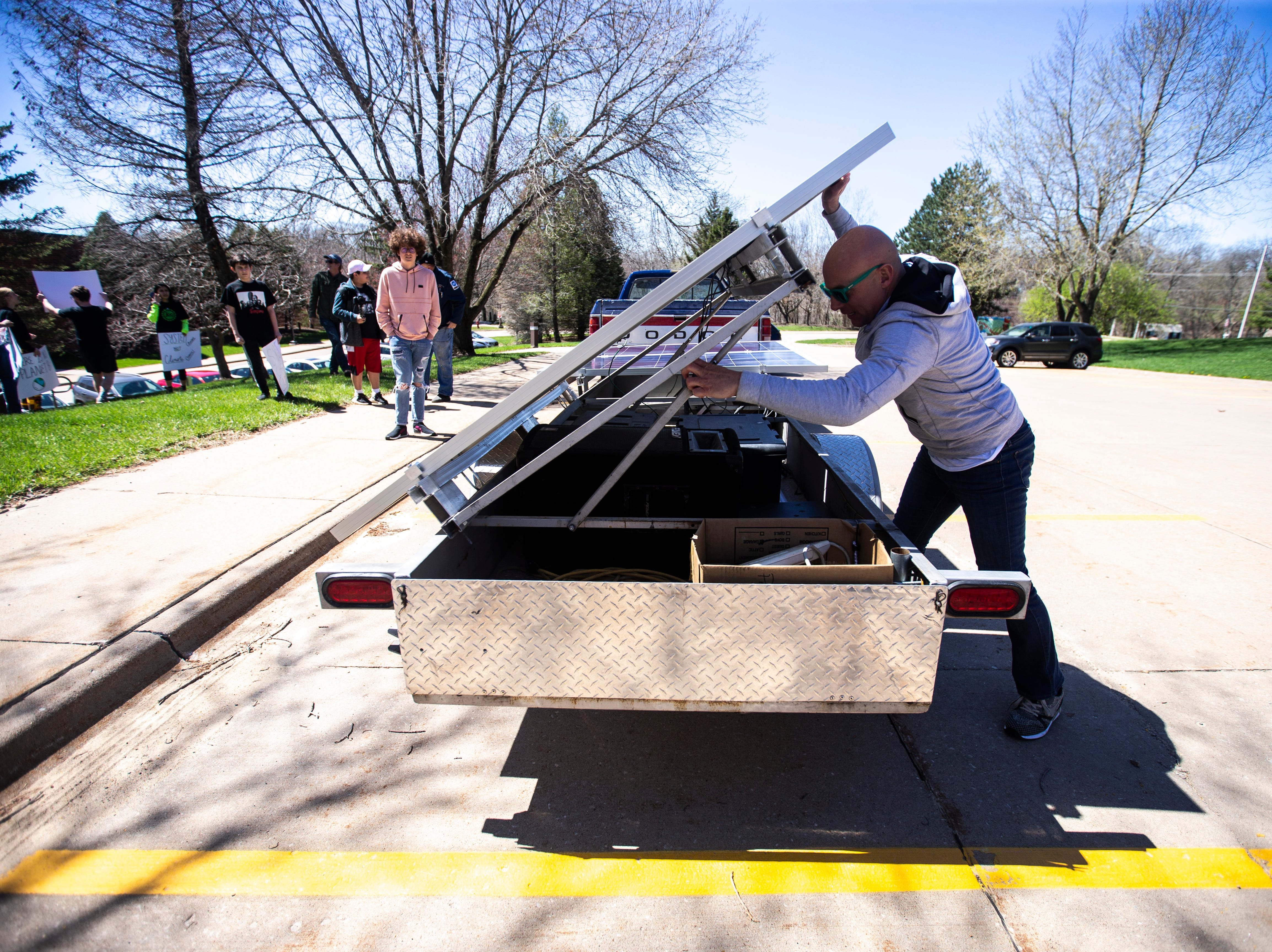 Former Hawkeye, NFL and City High star Tim Dwight sets up two of his solar panels while meeting with students during a weekly walkout demanding solar panels on school buildings, Friday, April 19, 2019, outside the Iowa City Community School District offices along North Dodge Street in Iowa City, Iowa.