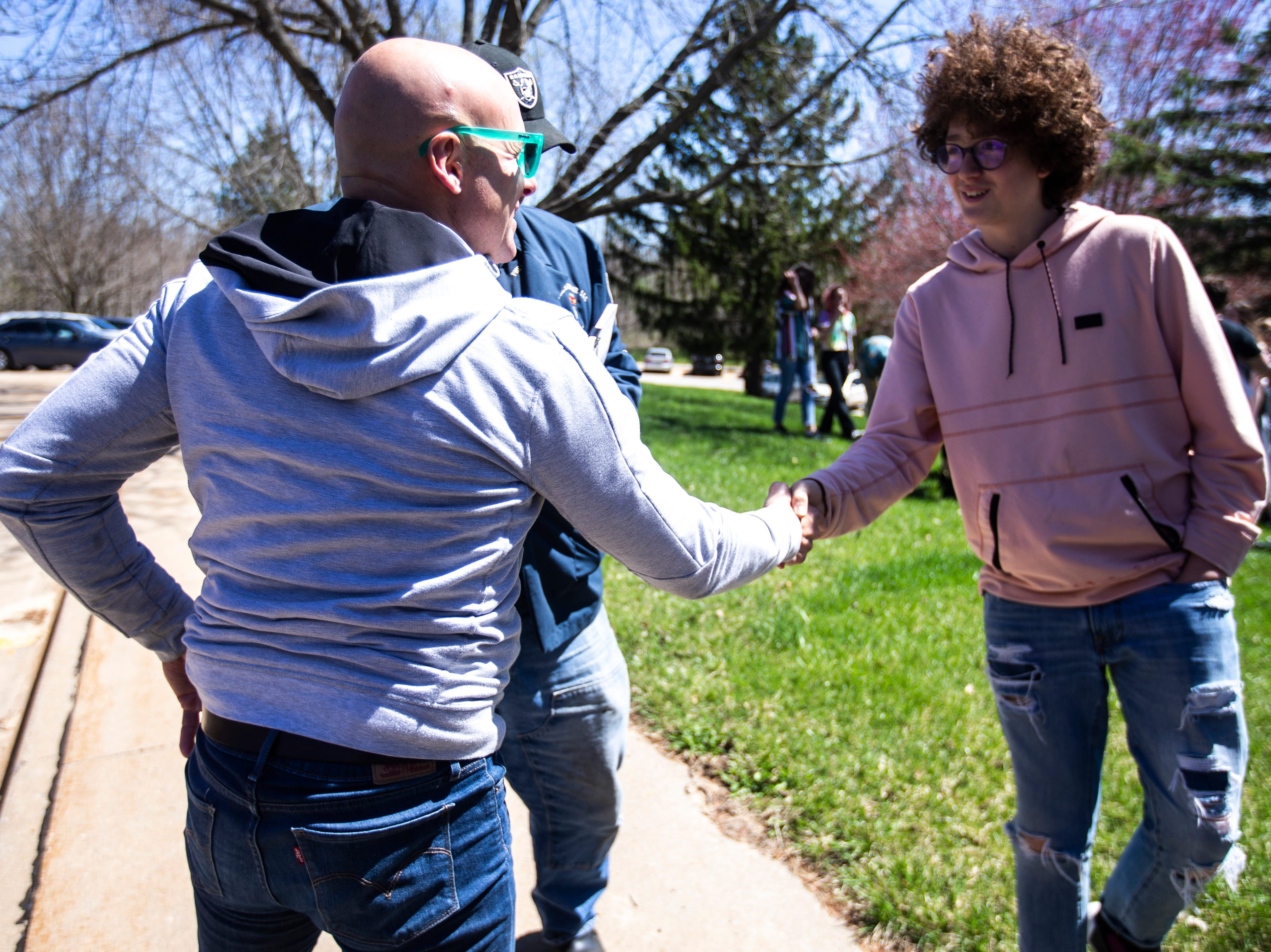 Former Hawkeye, NFL and City High star Tim Dwight shakes hands with Massimo Paciotto-Biggers, right, during a weekly walkout demanding solar panels on school buildings, Friday, April 19, 2019, outside the Iowa City Community School District offices along North Dodge Street in Iowa City, Iowa.