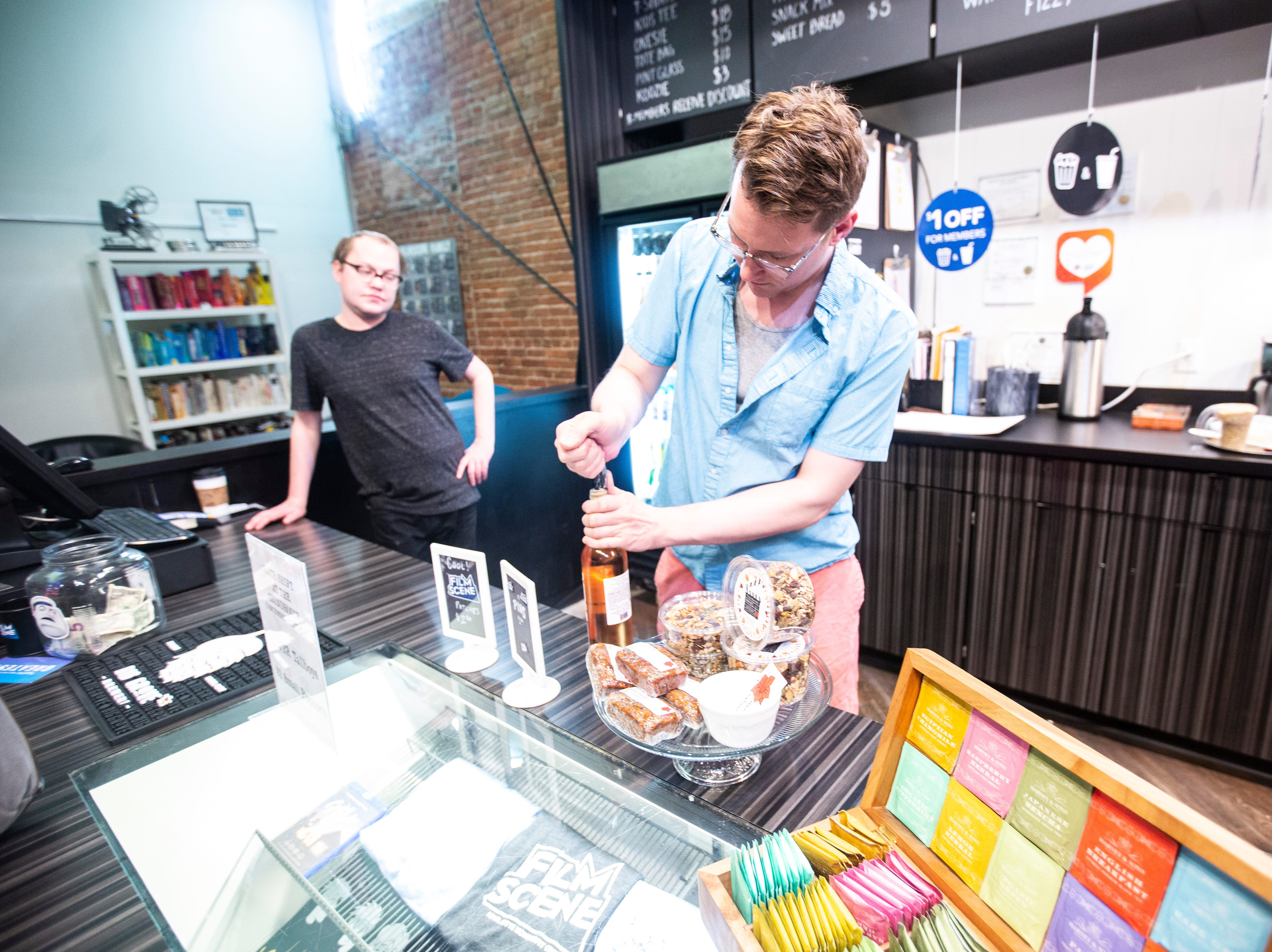 """Aaron Holmgren, assistant operations manager, opens a bottle of wine during a """"Late Shift at the Grindhouse"""" movie screening, Wednesday, April 17, 2019, at FilmScene in Iowa City, Iowa."""