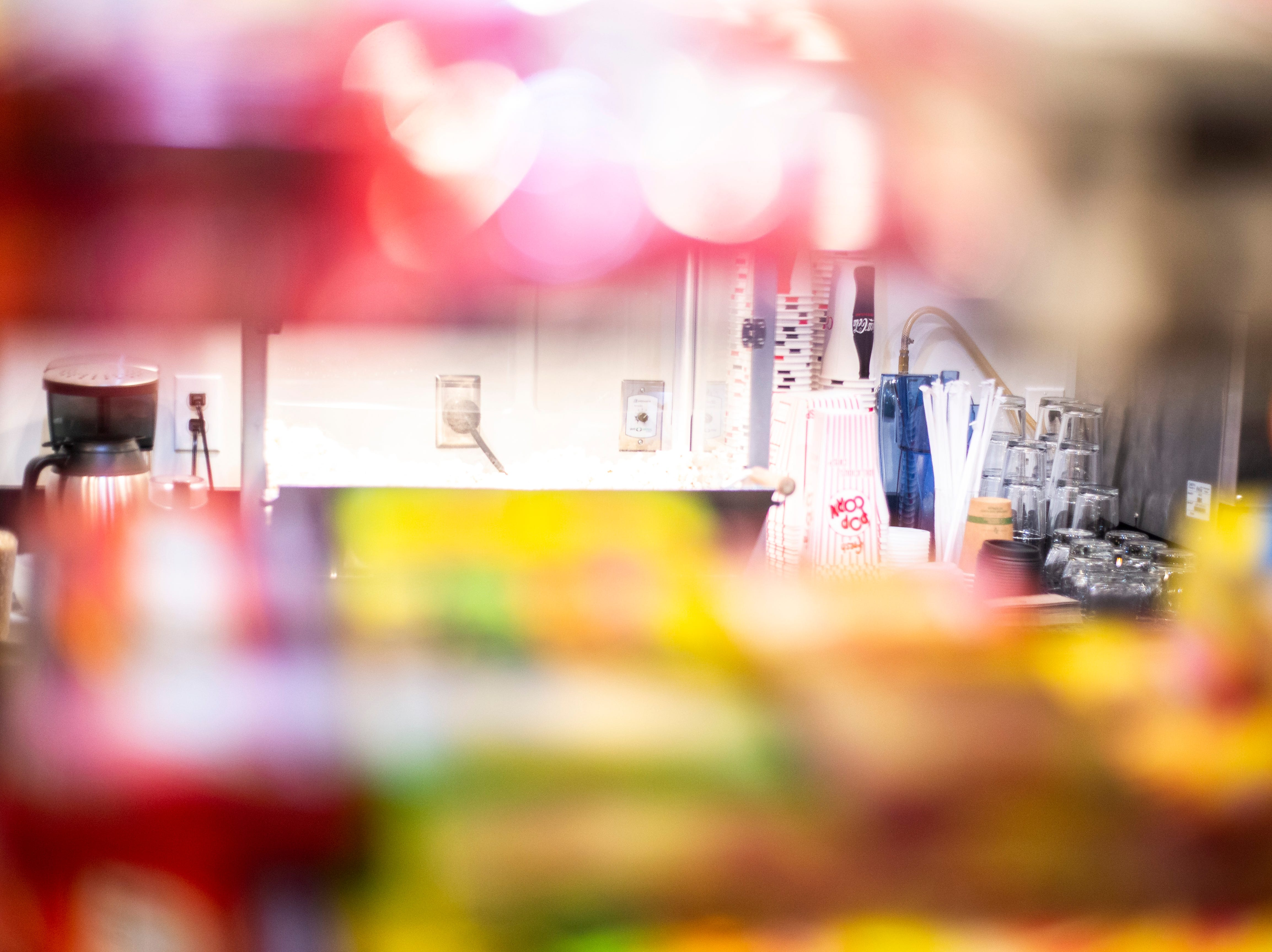 """A popcorn machine is seen through a rack of candy boxes during a """"Late Shift at the Grindhouse"""" movie screening, Wednesday, April 17, 2019, at FilmScene in Iowa City, Iowa."""