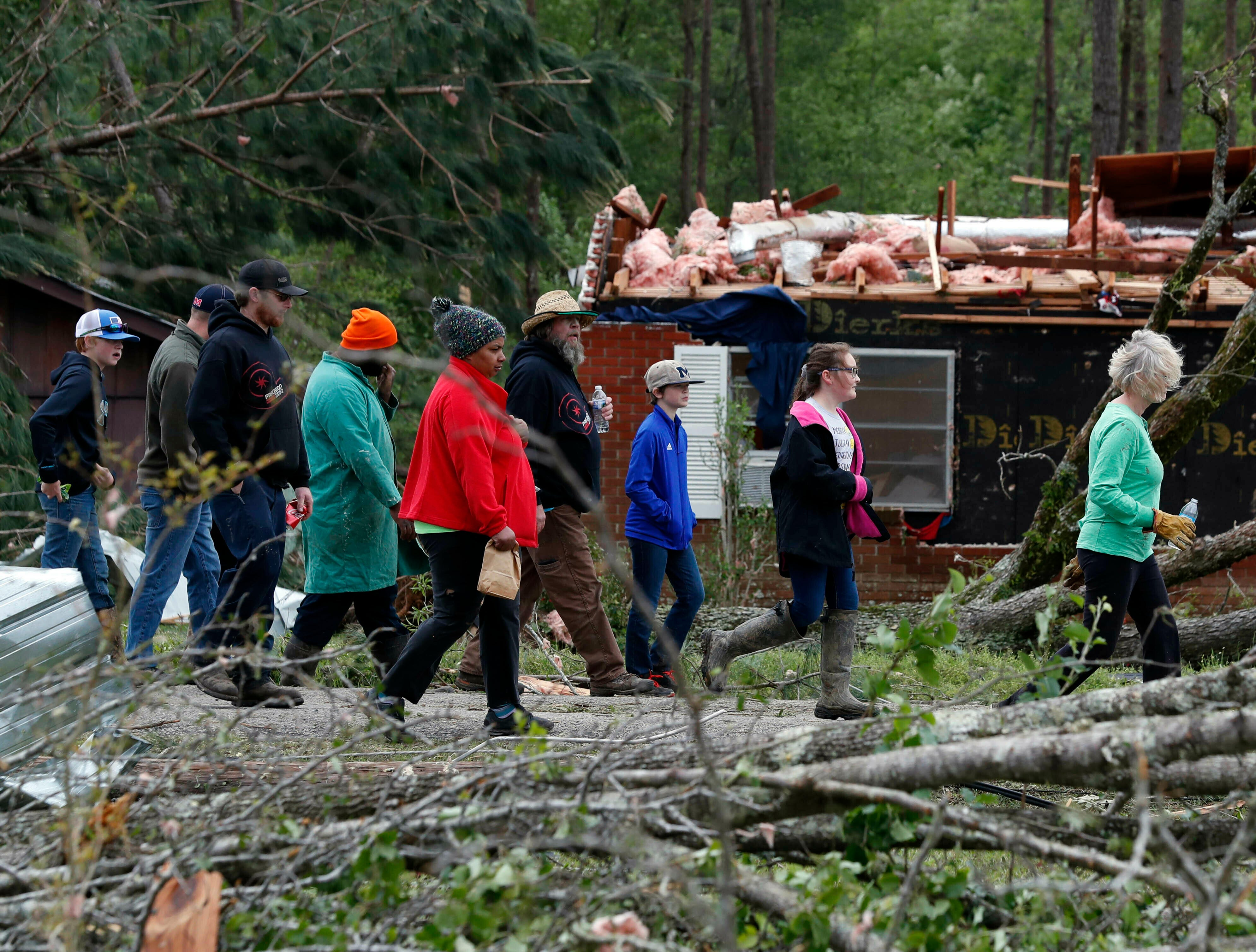 Morton, Miss., residents take a visual tour of their storm damaged neighborhood, Friday, April 19, 2019. Strong storms again roared across the South on Thursday, topping trees and leaving a variety of damage in Mississippi, Louisiana and Texas. (AP Photo/Rogelio V. Solis)