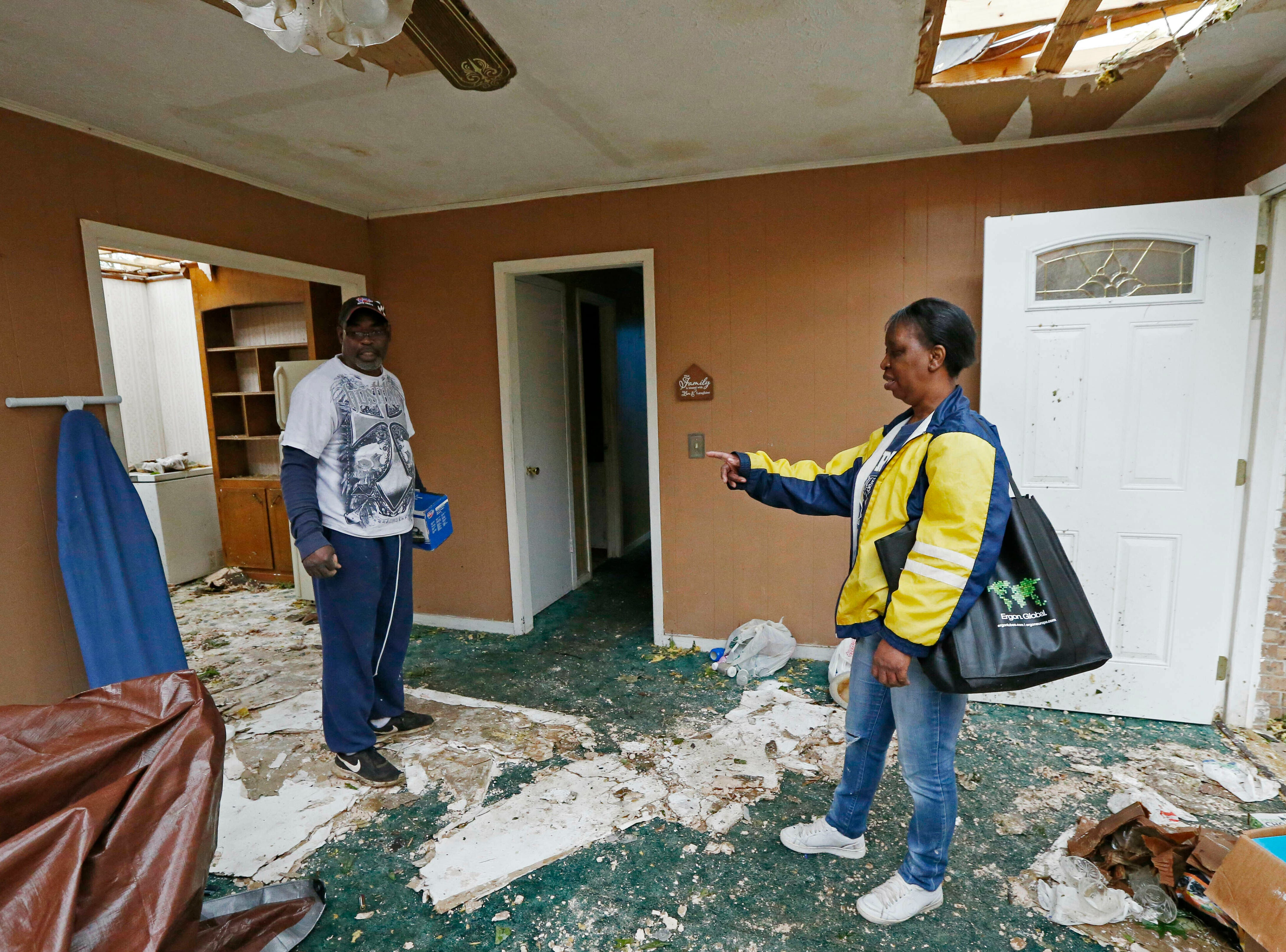 """""""Don't forget that ironing board,"""" calls out Morton, Miss., resident Sandra Toney, right to a friend as she tries to remove all salvageable items from her house, Friday, April 19, 2019, as she and other area residents begin the long road of physical recovery from being hit by a possible tornado, Thursday afternoon. Strong storms again roared across the South on Thursday, topping trees and leaving a variety of damage in Mississippi, Louisiana and Texas. (AP Photo/Rogelio V. Solis)"""
