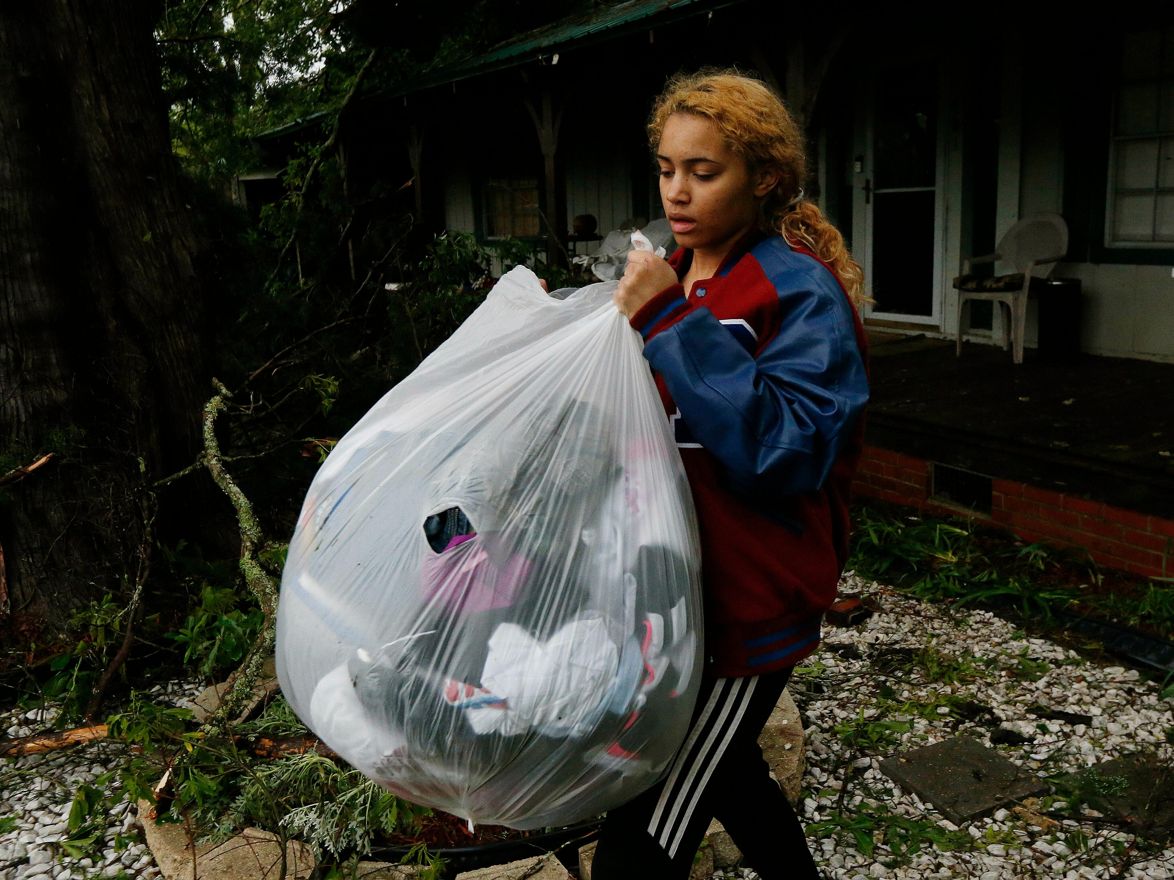 Hannah Claire carries out the unsoiled clothes of her friend Jacqualynn Qualls whose house was severely damaged by a fallen tree following severe weather that hit the small community of Learned, Miss., Thursday, April 18, 2019. Several homes were damaged by fallen trees in the tree lined community.