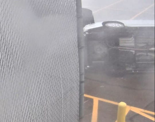 A video shows two vehicles being flipped over in Clinton's Walmart parking lot during a storm.