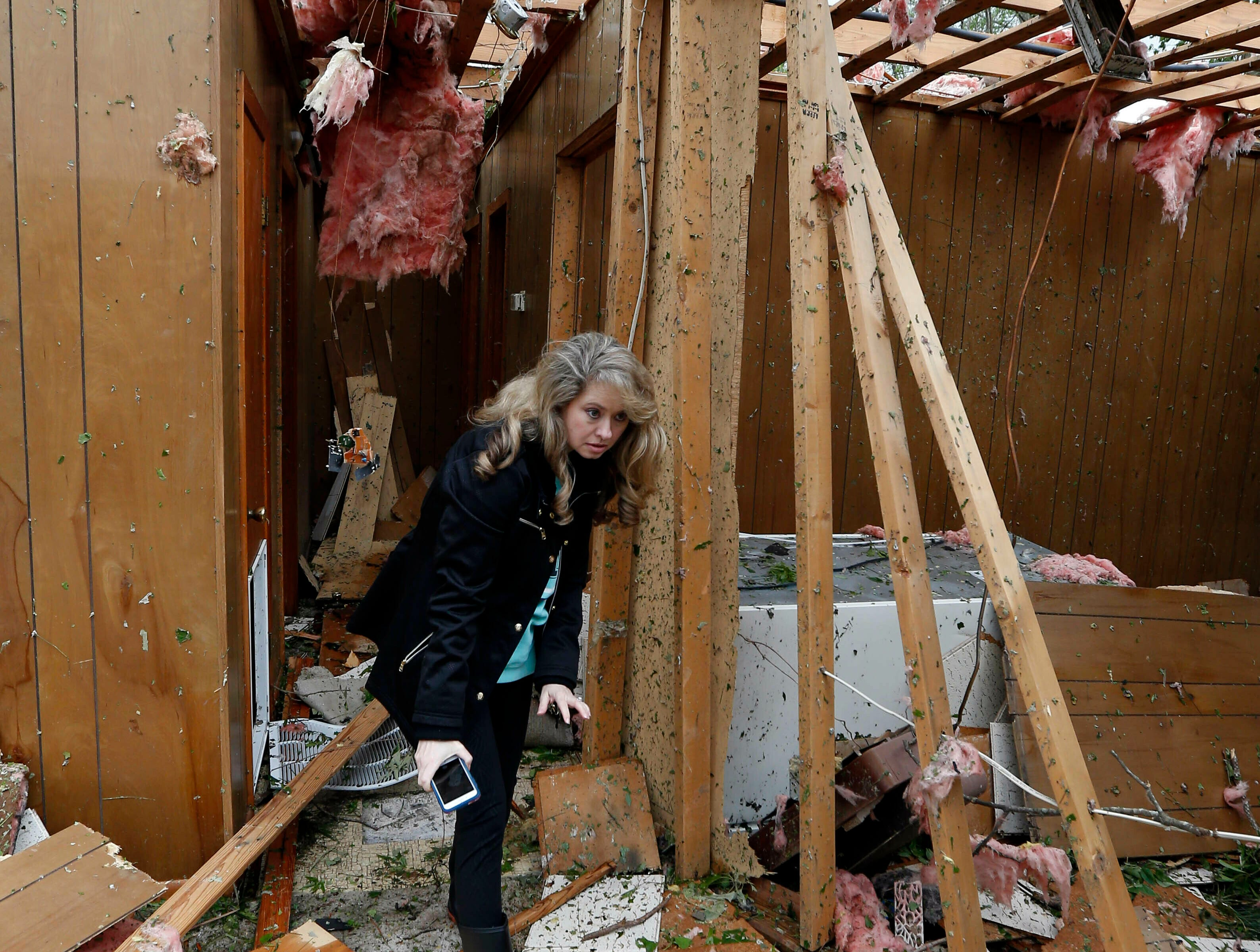 Tammy Phillips, walks through her storm damaged mother's house, Friday, April 19, 2019, in Morton, Miss. The house, unoccupied for about a year, was destroyed by a possible tornado Thursday afternoon. Strong storms again roared across the South on Thursday, topping trees and leaving a variety of damage in Mississippi, Louisiana and Texas. (AP Photo/Rogelio V. Solis)