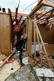 Tammy Phillips, walks through her storm damaged mother's house, Friday, April 19, 2019, in Morton, Miss.