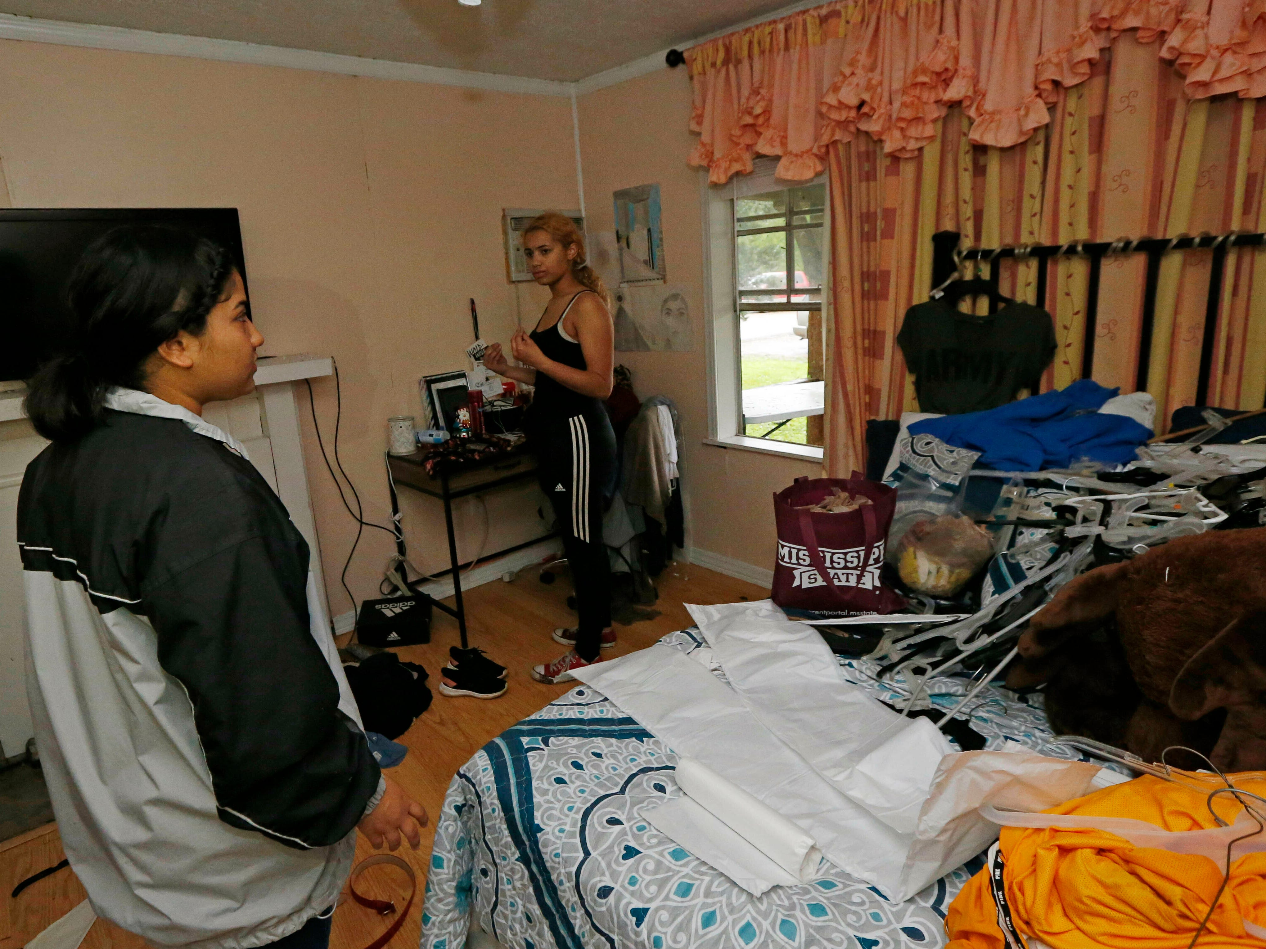 Jacqualynn Qualls, left, gathers her clothes from her undamaged room in her Learned, Miss., home, Thursday, April 18, 2019, after a oak tree demolished her brother's room, bathroom and much of the living quarters. Strong storms again roared across the South on Thursday, topping trees and leaving more than 100,000 people without power across Mississippi, Louisiana and Texas.