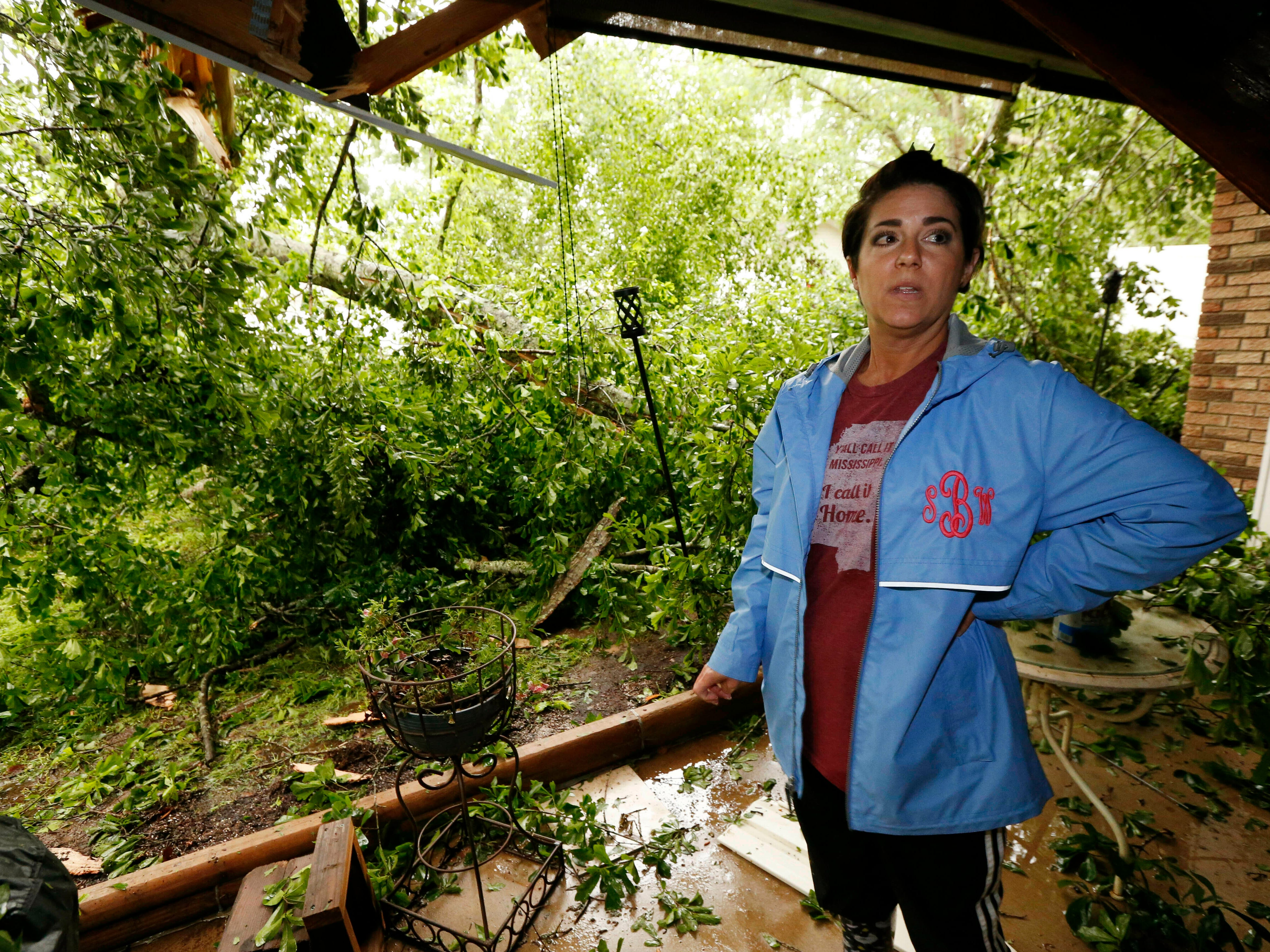 Sonya Banes reacts to a large oak tree that crashed through the patio of her mother's house in Learned, Miss., Thursday, April 18, 2019. Several homes were damaged by fallen trees in the community.