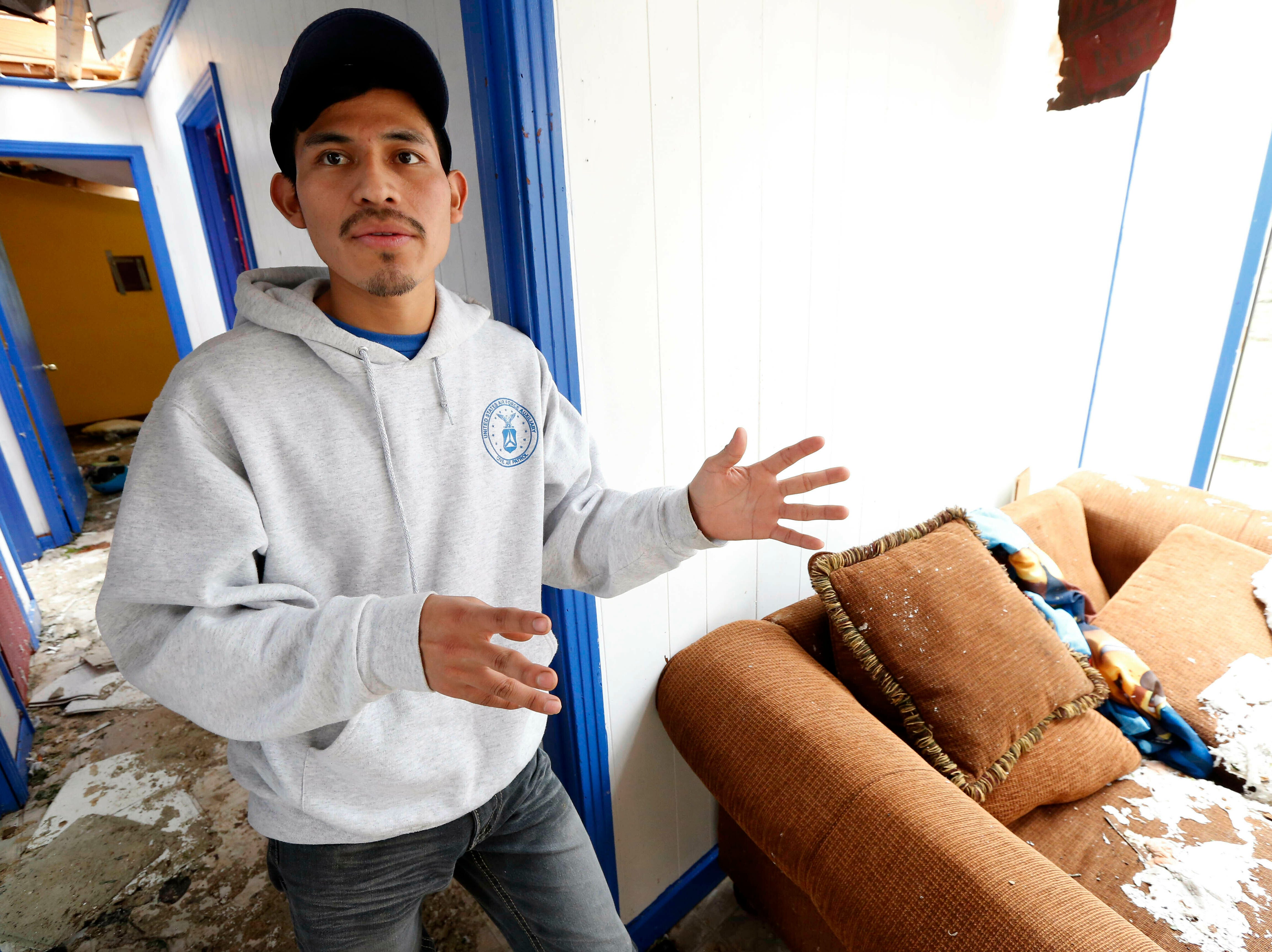 Andres Aguilar, a native of Guatemala, says Friday, April 19, 2019, that he and other family members were very scared when they heard the winds of a possible tornado hit their Morton, Miss., home, Thursday afternoon. Augilar said he and his family hid under the house's door frame as much of the roof was torn off and the windows were blown out. Strong storms again roared across the South on Thursday, topping trees and leaving a variety of damage in Mississippi, Louisiana and Texas. (AP Photo/Rogelio V. Solis)