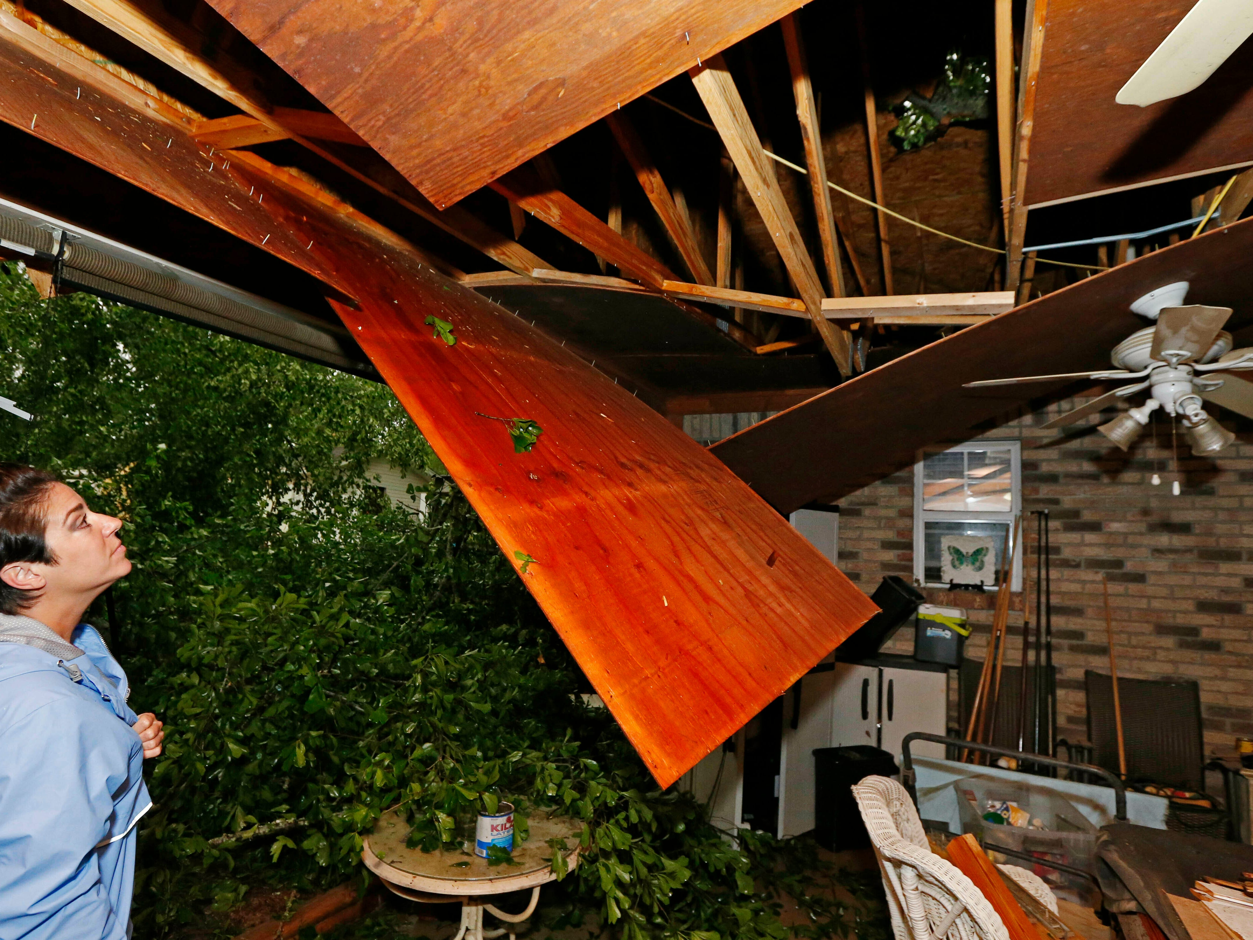 Sonya Banes looks at damage caused by a large oak tree that crashed through the ceiling of her mother's house in Learned, Miss., Thursday, April 18, 2019. Several homes were damaged by fallen trees in the tree lined community. Strong storms again roared across the South on Thursday, topping trees and leaving more than 100,000 people without power across Mississippi, Louisiana and Texas.