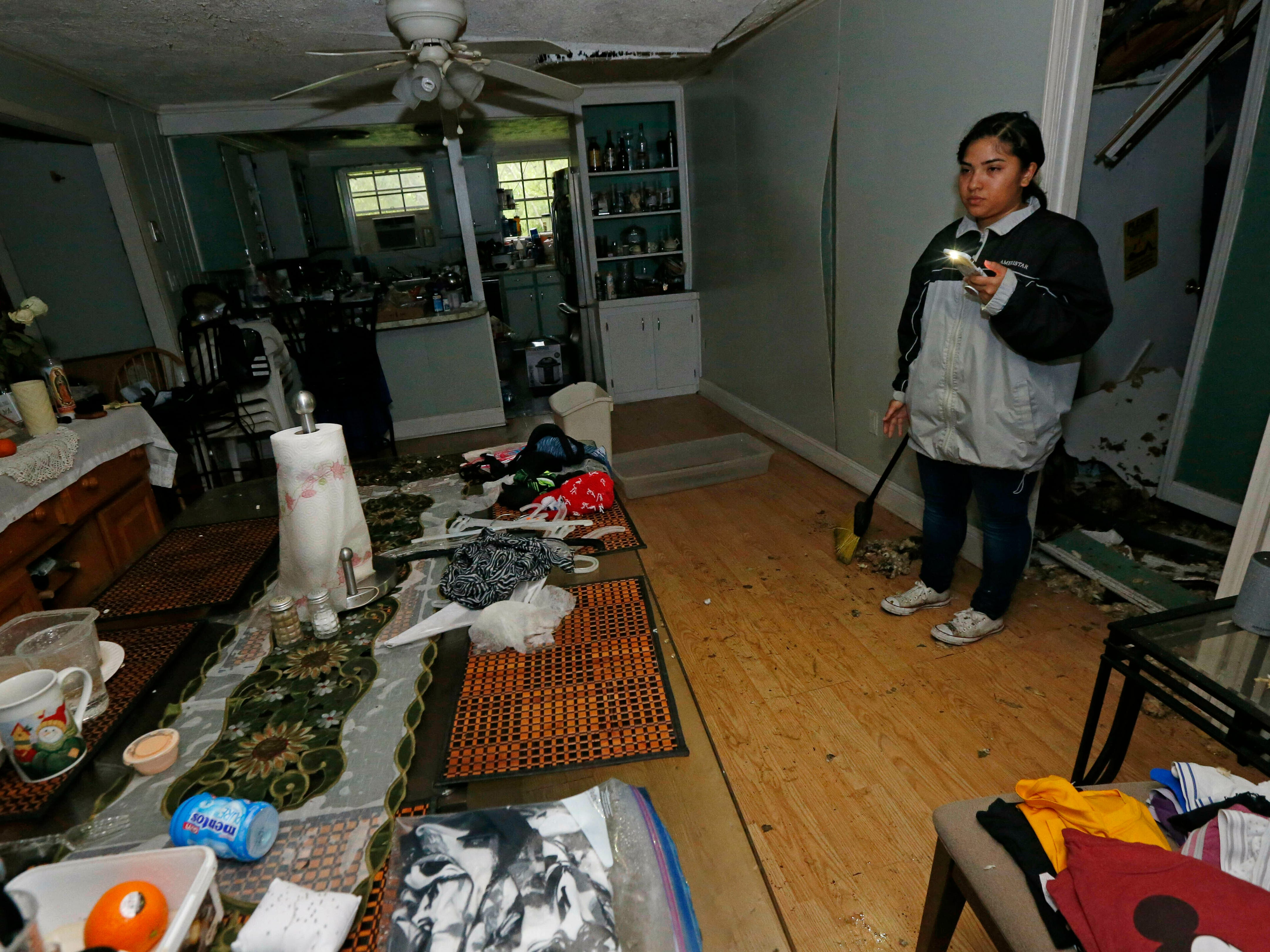 Jacqualynn Qualls calls to her mother in the tree-damaged living room of their Learned, Miss., home, following severe weather that hit the small community, Thursday, April 18, 2019. Several homes were damaged by fallen trees in the tree lined community. Strong storms again roared across the South on Thursday, topping trees and leaving more than 100,000 people without power across Mississippi, Louisiana and Texas.