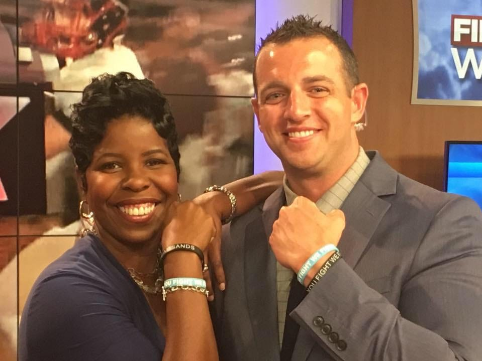"""WDBD Fox 40 anchors Melissa Faith Payne and Mike Sands show off their """"YOU FIGHT, WE FIGHT"""" rubber bracelets in support of Sands' fight against cancer."""