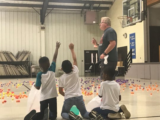 West Jackson Baptist Church's Alan Teel talks about the Easter egg hunt to students at Pope Elementary School on Thursday as students raise their hand to ask a question.