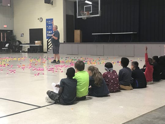 Students wait patiently before being given the go-ahead to grab eggs during the Easter egg hunt at Pope Elementary on Thursday.