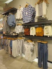 Chic clothing and bags line the walls at the West Town Bliss.