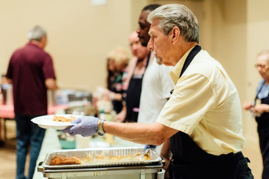 Mitch Murphy serves supper to guests at Recovery, a ministry of Powell Church.