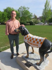 Dalton Teel, one of the UT students involved in the Smokey statues project, poses next to Smokey II in Circle Park on April 17.