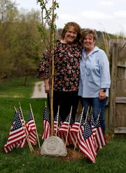 Jodi Smith, left, and Beth Kehrer, coworkers of Teri Mecionis at Fairfield County Job and Family Services, stand next to a tree they planted in the back yard Mecionis's home in Lancaster.