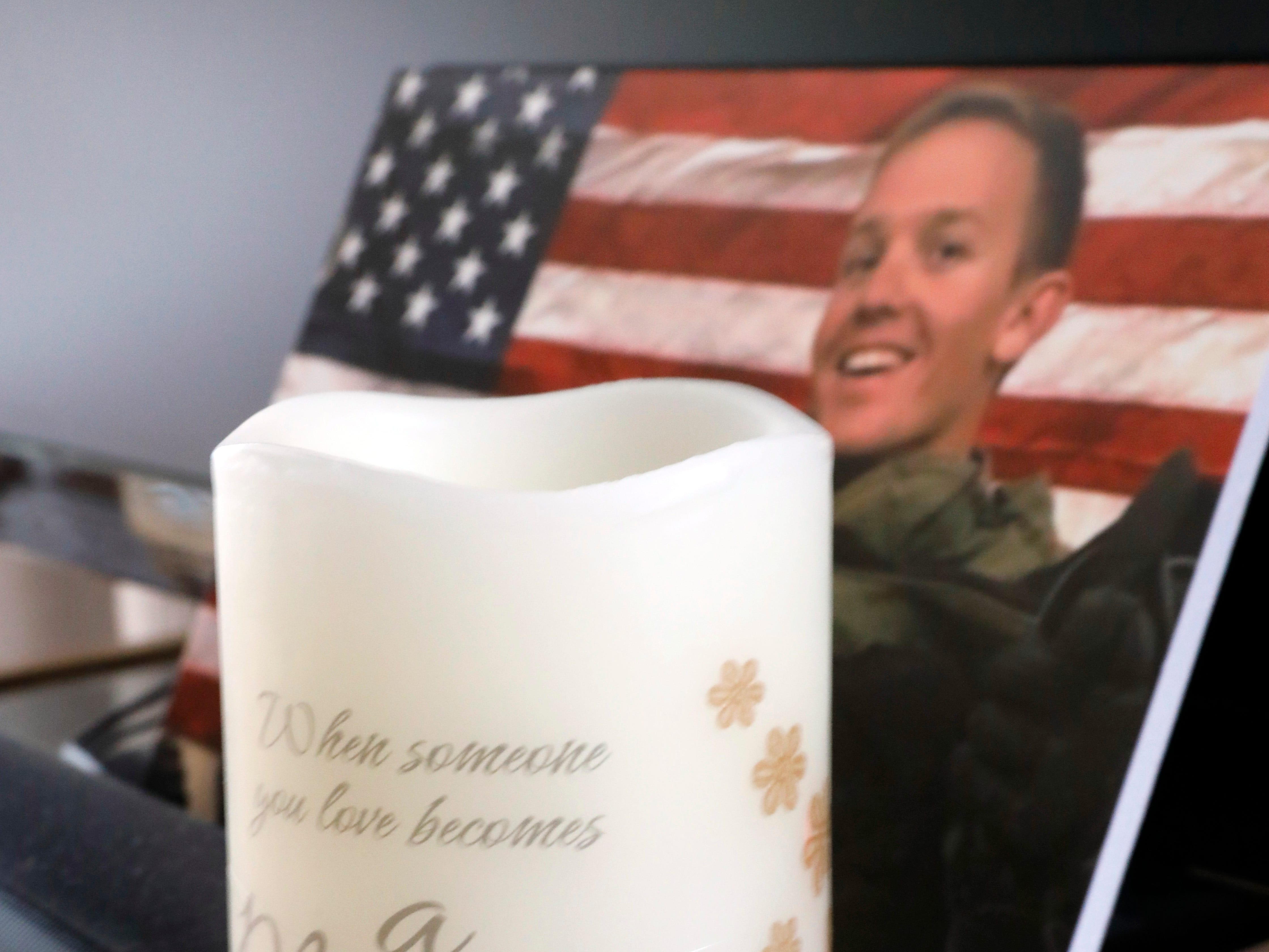 A candle sits in front of a photograph Sgt. Joseph Collette in the home of his mother Teri Mecionis in Lancaster.