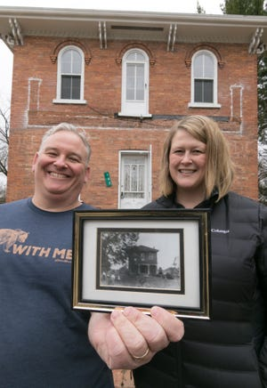 Dan and Anna Oginsky stand in front of the home on Brighton Lake Road, which will house their Brighton Light House project. Dan holds a photograph showing the home that is believed to have been taken shortly after the home was built in 1862.
