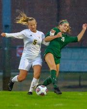 Hartland's Maria Storm (5) and Novi's Jessica Bandyk (16) battle for the soccer ball on Thursday, April 18, 2019.