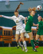 Novi's Avery Fenchel, who had a goal and two assists, gets a header in front of Hartland's Michelle Keranen (11) on Thursday, April 18, 2019.