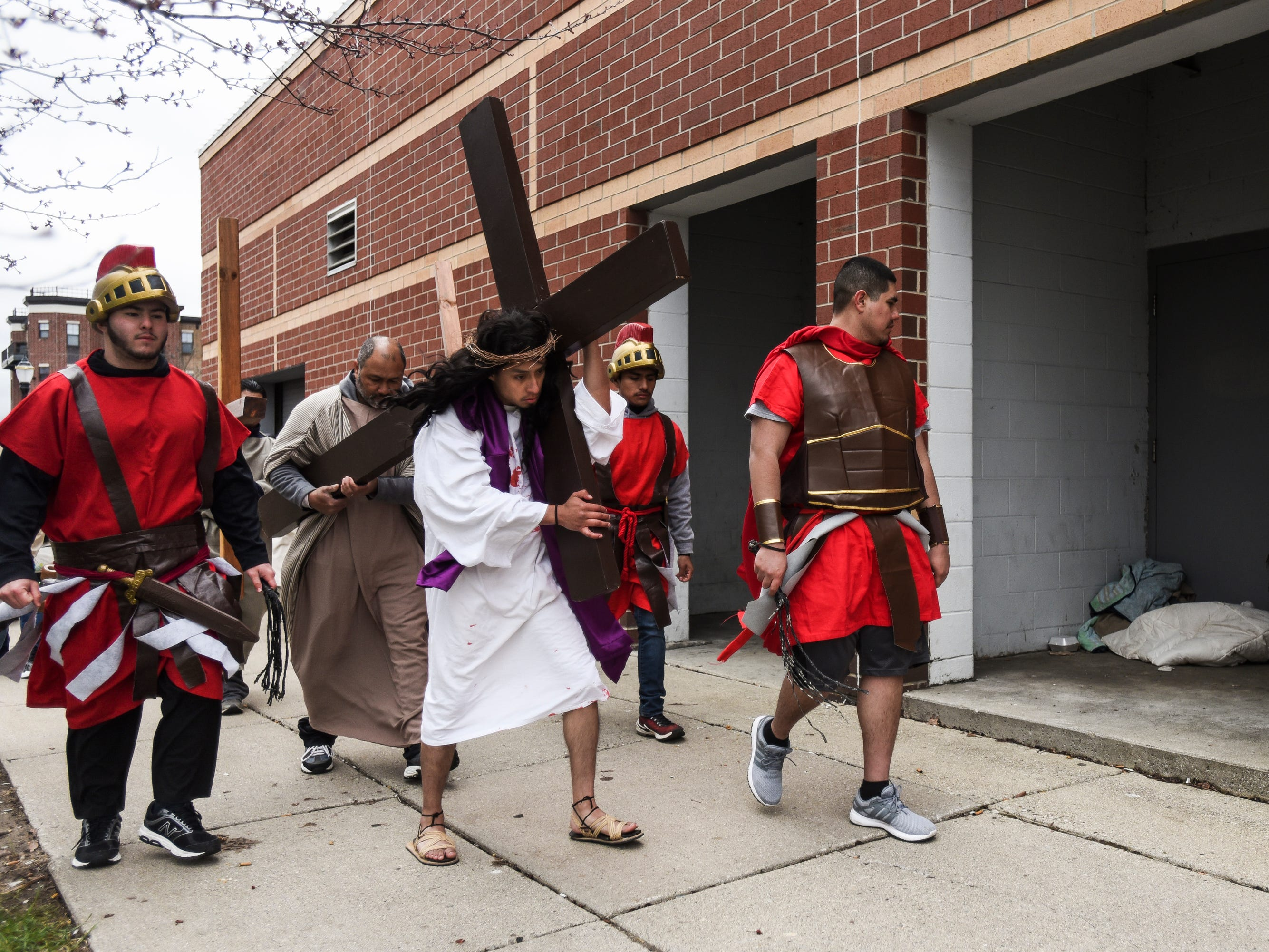 """David Ponce, portraying Jesus, carries a cross through downtown Lansing past Cooley Law School Stadium as Cristo Rey's """"Stations of the Cross"""" Friday, April 19, 2019.  The service started on the steps of the Capitol with the reenactment of Jesus being condemned to death and concluded at the Cristo Rey Community Center with the crucifixion followed by a Good Friday service."""