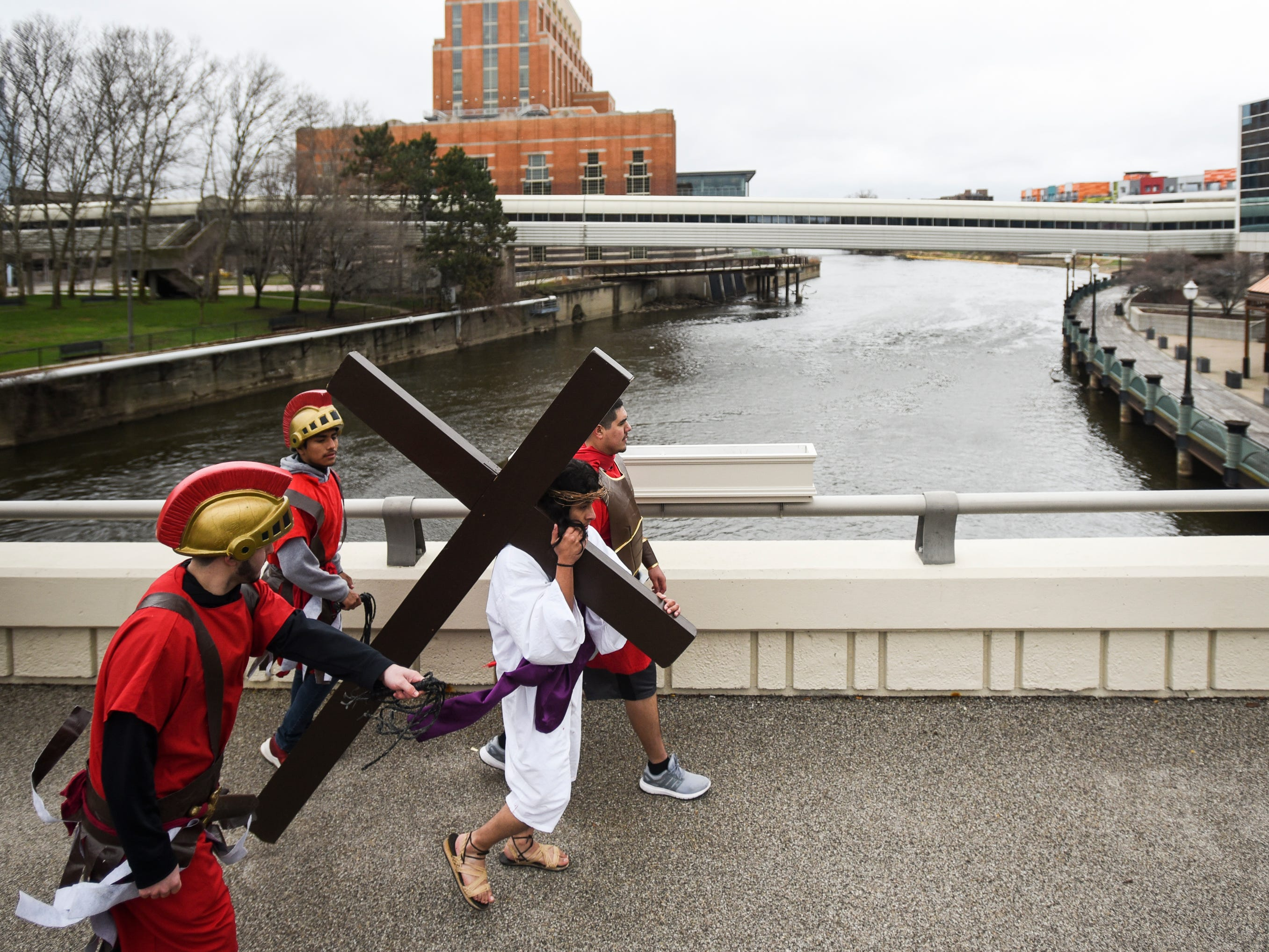 """David Ponce, portraying Jesus, carries a cross through downtown Lansing along Michigan Avenue over the Grand River as part of Cristo Rey's """"Stations of the Cross,"""" Friday, April 19, 2019.  The service started on the steps of the Capitol with the reenactment of Jesus being condemned to death and concluded at the Cristo Rey Community Center with the crucifixion followed by a Good Friday service."""