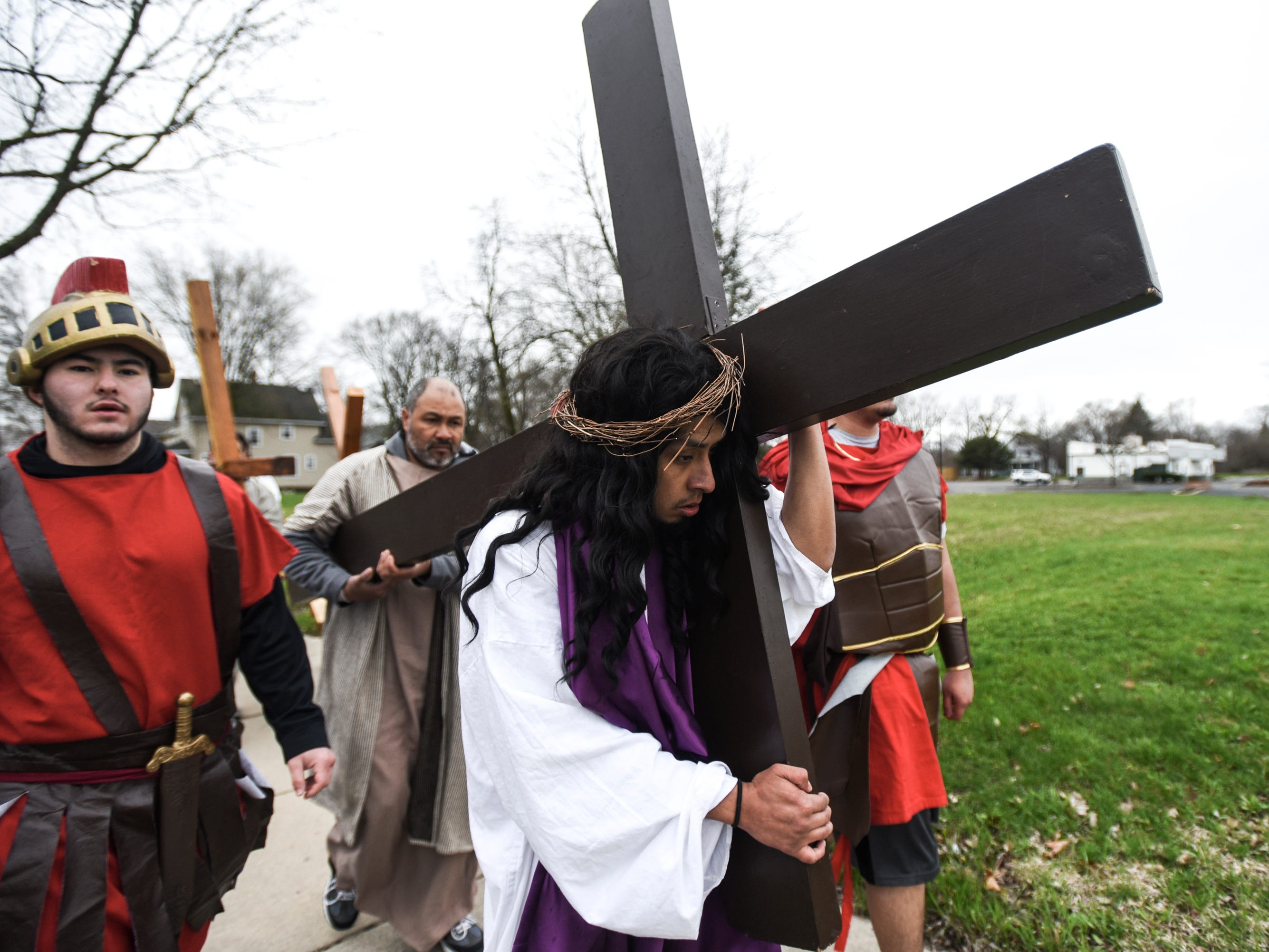 """David Ponce, portraying Jesus, carries a cross through downtown Lansing along N. Larch Street as part of Cristo Rey's """"Stations of the Cross,"""" Friday, April 19, 2019.  The service started on the steps of the Capitol with the reenactment of Jesus being condemned to death and concluded at the Cristo Rey Community Center with the crucifixion followed by a Good Friday service."""