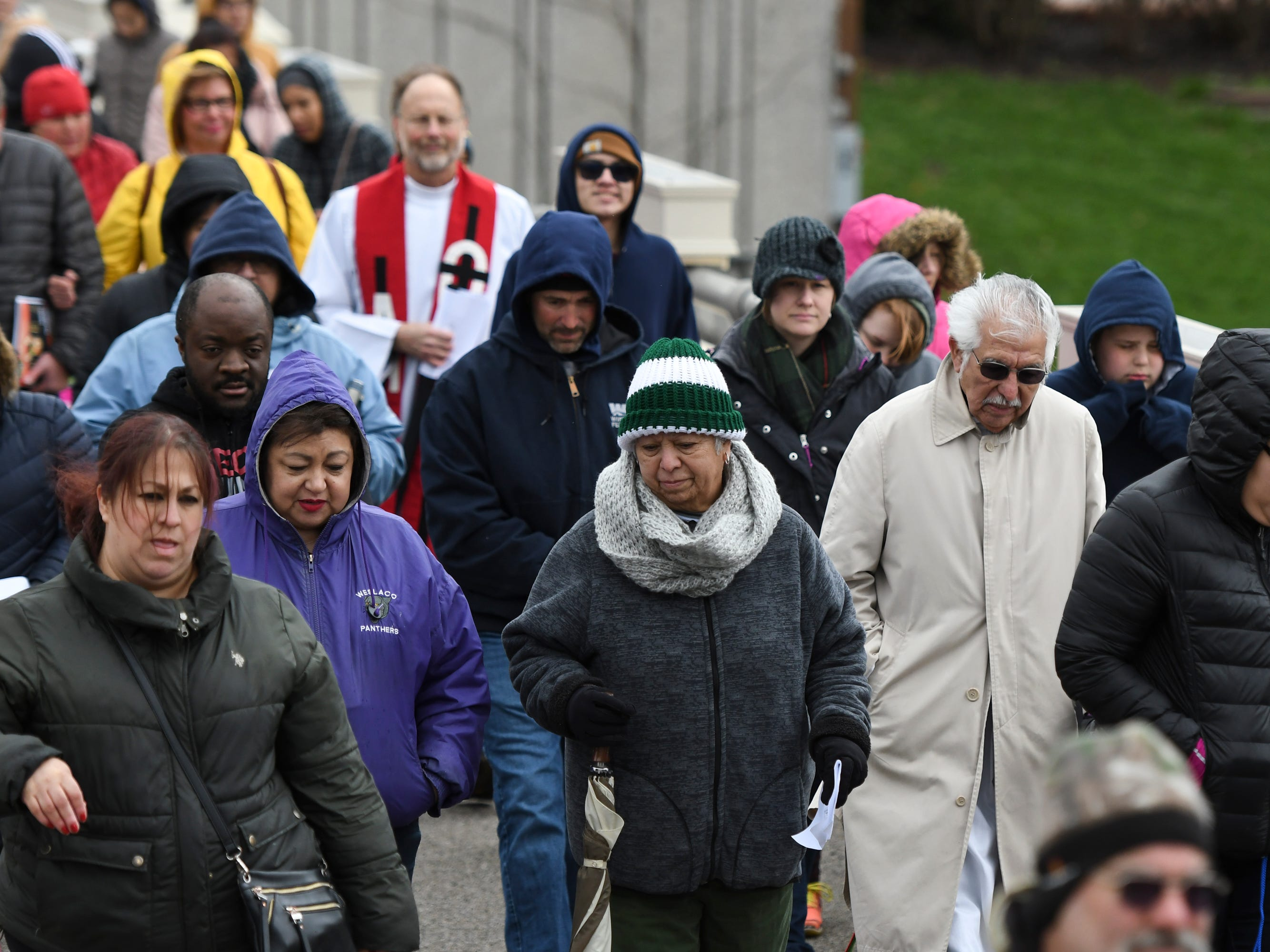 """A small crowd follows David Ponce who portrayed as Jesus as he carries a cross through downtown Lansing as part of Cristo Rey's """"Stations of the Cross,""""  Friday, April 19, 2019.  The service started on the steps of the Capitol with the reenactment of Jesus being condemned to death and concluded at the Cristo Rey Community Center with the crucifixion followed by a Good Friday service."""