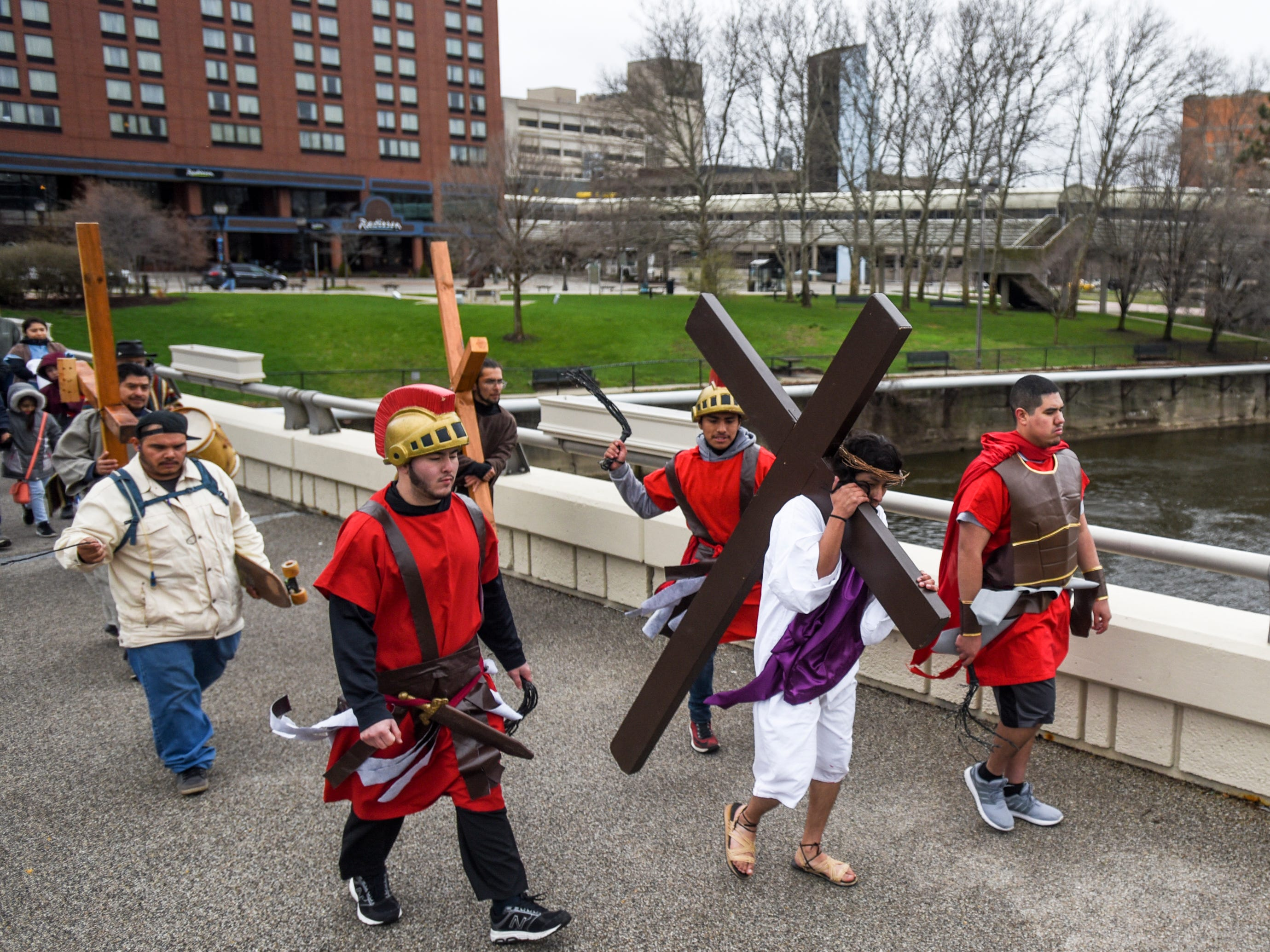 """David Ponce, portraying Jesus, carries a cross through downtown Lansing as part of  Cristo Rey's """"Stations of the Cross,"""" Friday, April 19, 2019.  The service started on the steps of the Capitol with the reenactment of Jesus being condemned to death and concluded at the Cristo Rey Community Center with the crucifixion followed by a Good Friday service."""