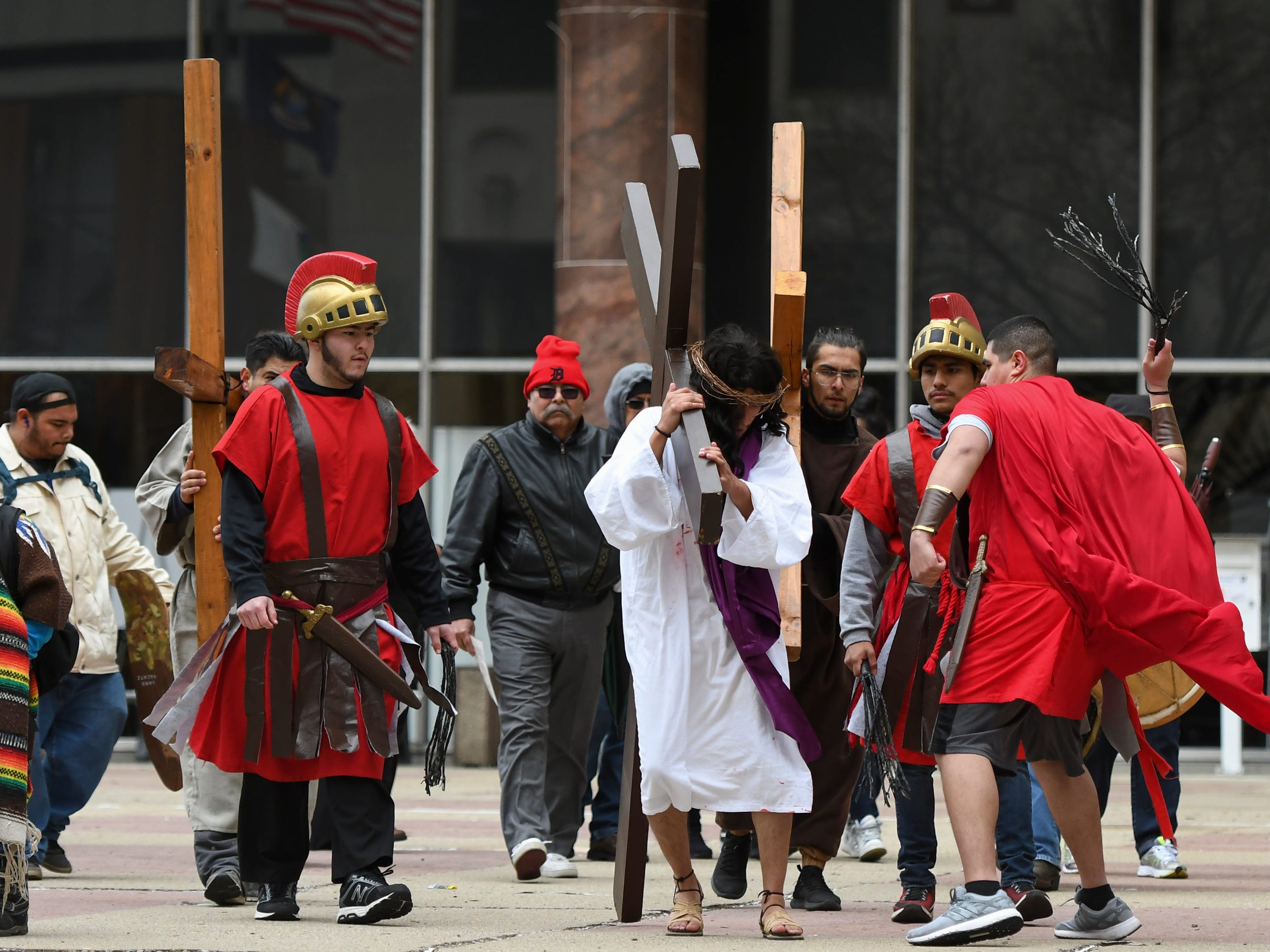 """David Ponce, portraying Jesus, carries a cross as part of Cristo Rey's """"Stations of the Cross,"""" Friday, April 19, 2019.  The service started on the steps of the Capitol with the reenactment of Jesus being condemned to death and concluded at the Cristo Rey Community Center with the crucifixion followed by a Good Friday service."""