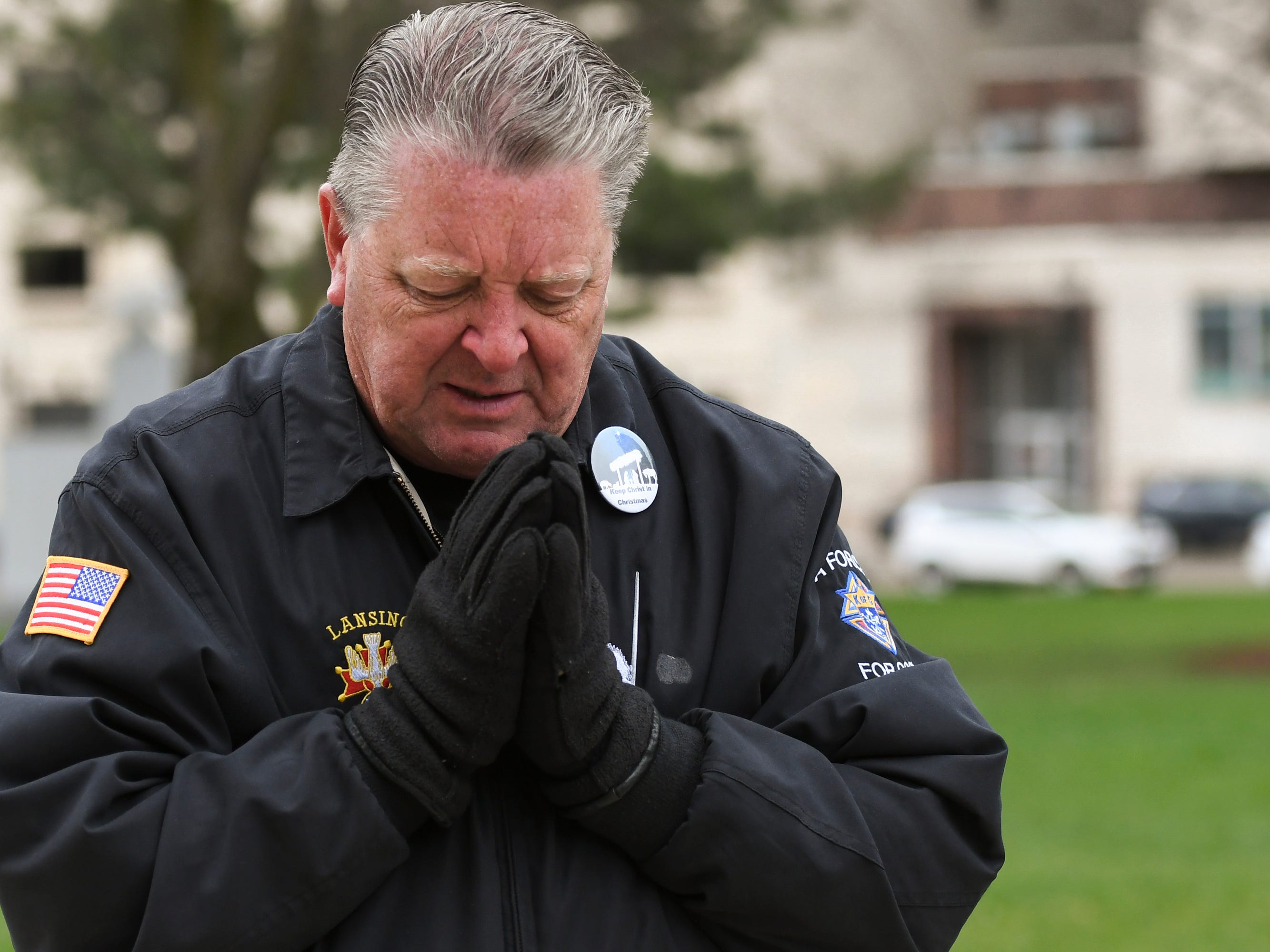 """Daniel Reine prays on Good Friday, April 19, 2019, outside of the State Capitol where Cristo Rey presented """"Stations of the Cross."""""""