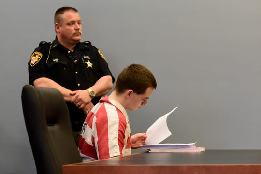 Caleb Sampsel, 18, looks over his file Friday before being sentenced to 25 years in prison.
