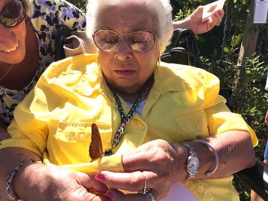 Lena Molinari watches as a butterfly lands on her hand before it flies away to feed on the many nectar plants in the Butterfly Garden.