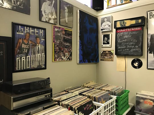 An early version of Giannis Antetokounmpo hangs on the wall at On the Beaten Path record store in Bay View.