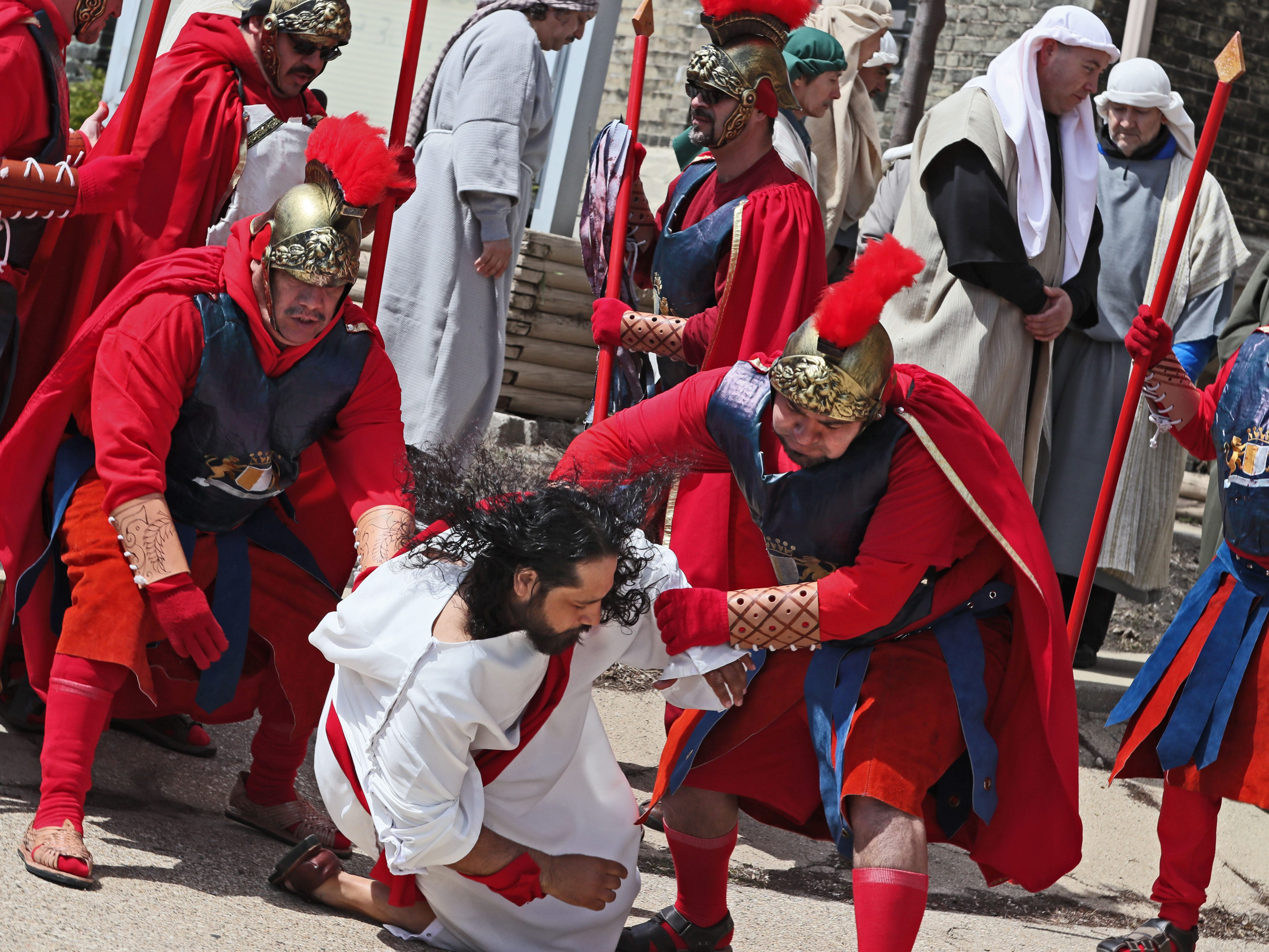 Roman soldiers throw Jesus to the ground after arresting him during a re-enactment of the Passion of Jesus Christ on Good Friday. Jesus is played by Pedro Rangel of Milwaukee.