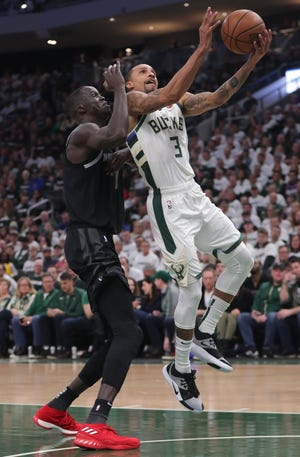 Bucks guard George Hill gets past  the Pistons' Thon Maker for a shot in Game 1.