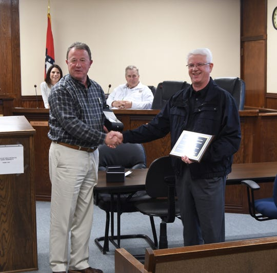 Mountain Home Mayor Hillrey Adams (left) presented Police Chief Carry Manuel (right) with a plaque and a watch Thursday night at the City Council's April meeting. Manuel has worked for the city for 35 years.
