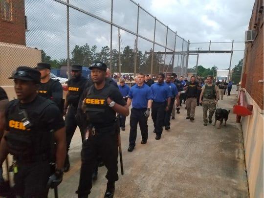 Officers enter Holman prison on April 18, 2019.