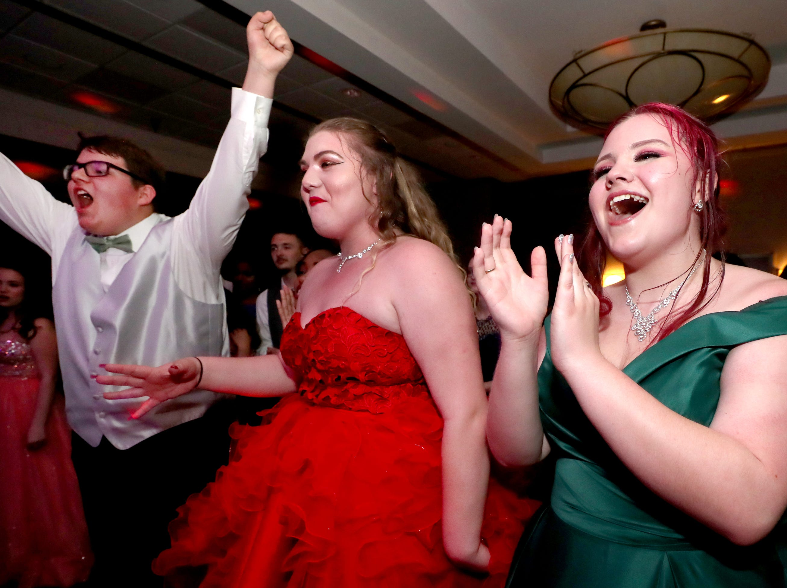 Nate Steinhurst, left, Cortney Springer center, and Evie Douglas, right react as Diego Valencia is announced as Holloway High's Prom King at Holloway's prom at the DoubleTree on Thursday April 18, 2019.