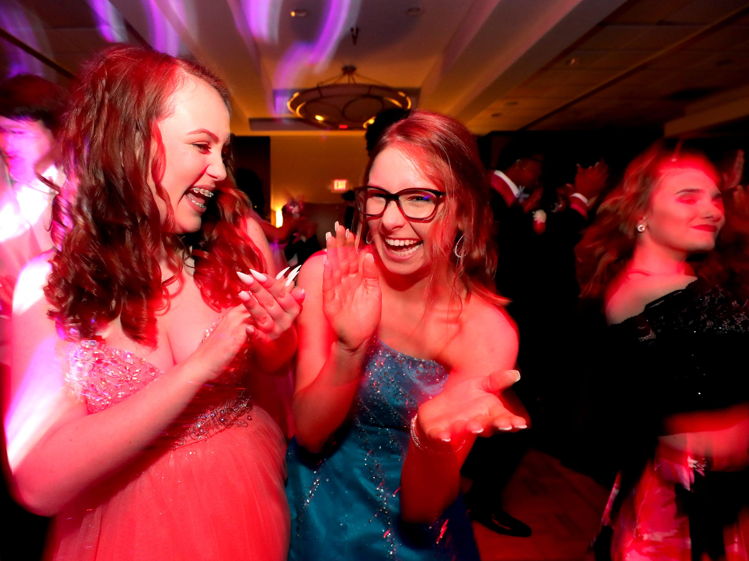 Abby Carr, left and Erin Carlson, right dance on the dance floor at Holloway's prom at the DoubleTree on Thursday April 18, 2019.